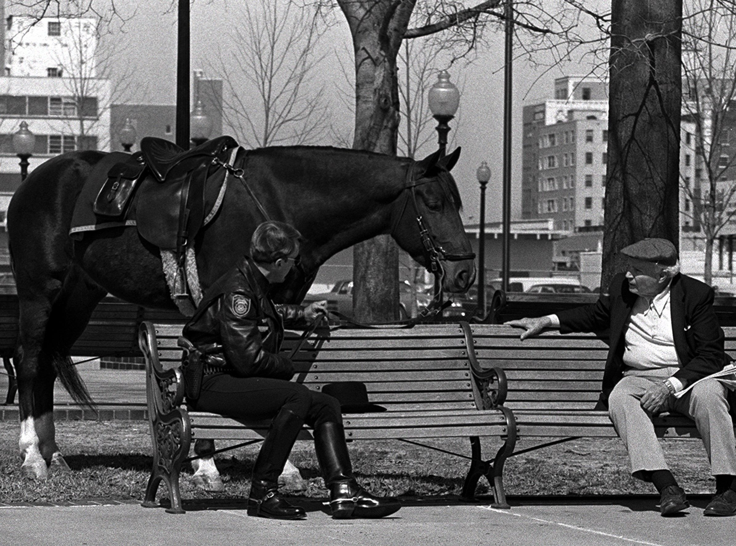 Mounted patrolman J.B. Dyer sits on a bench in W.C. Handy Park on 17 Mar 1985, talking to another Beale Street bench sitter, John Rea, as Dyer's horse, C.J. stands by, enjoying the weather too.