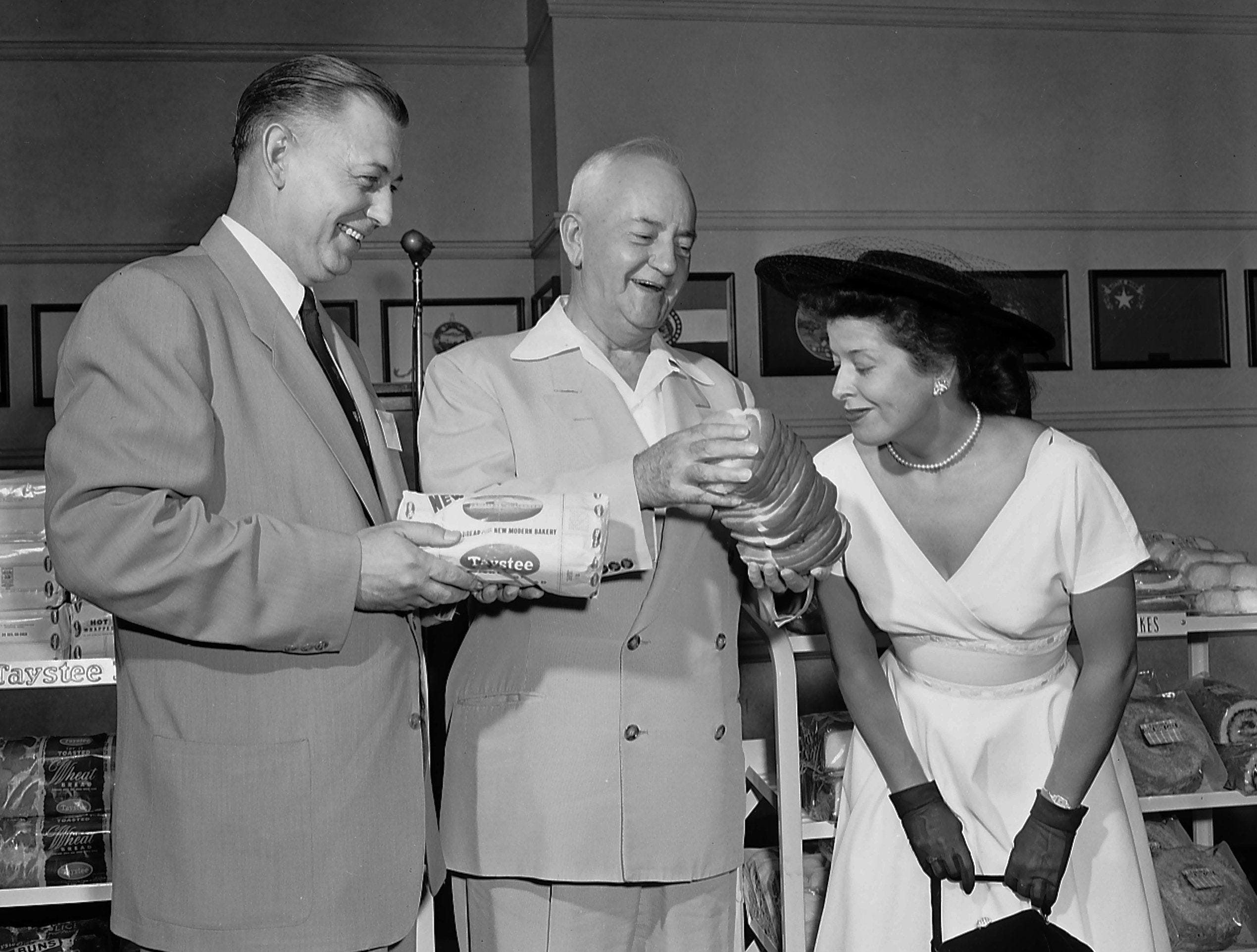 Mayor Frank Tobey, center, beamingly offers Mrs. Regina Webb of 515 South Barksdale a sniff of the new loaf of Taystee bread introduced at a luncheon at the Peabody in June 1953. M.J. Curry, manager of Taystee, looks on.