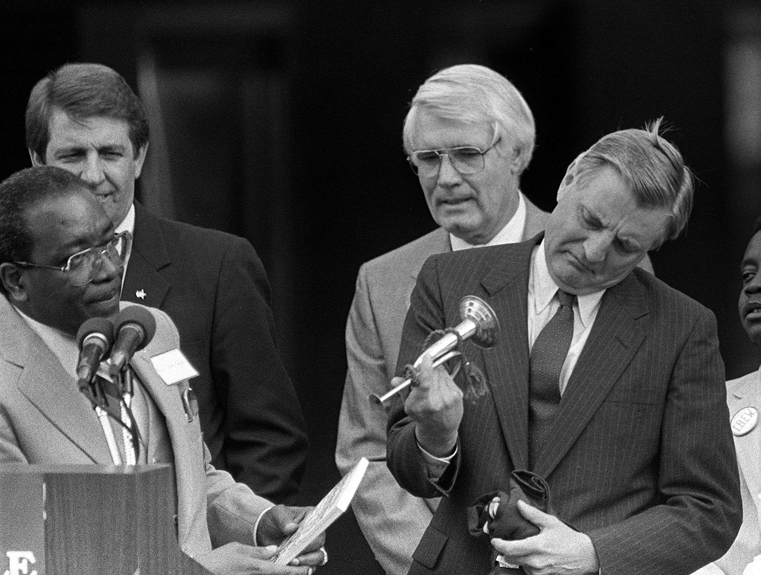 "Democratic Presidential candidate Walter Mondale, attempting to toot his Beale Street horn during an appearance in Memphis on 28 Apr 1984, had to look down the bell of his tiny bugle when no sound came out. Looking on are Rev. James Smith (Left), Shelby County Mayor William N. Morris Jr. (Back Left) and Robert C. ""Bobby"" Lanier (Second Right)."