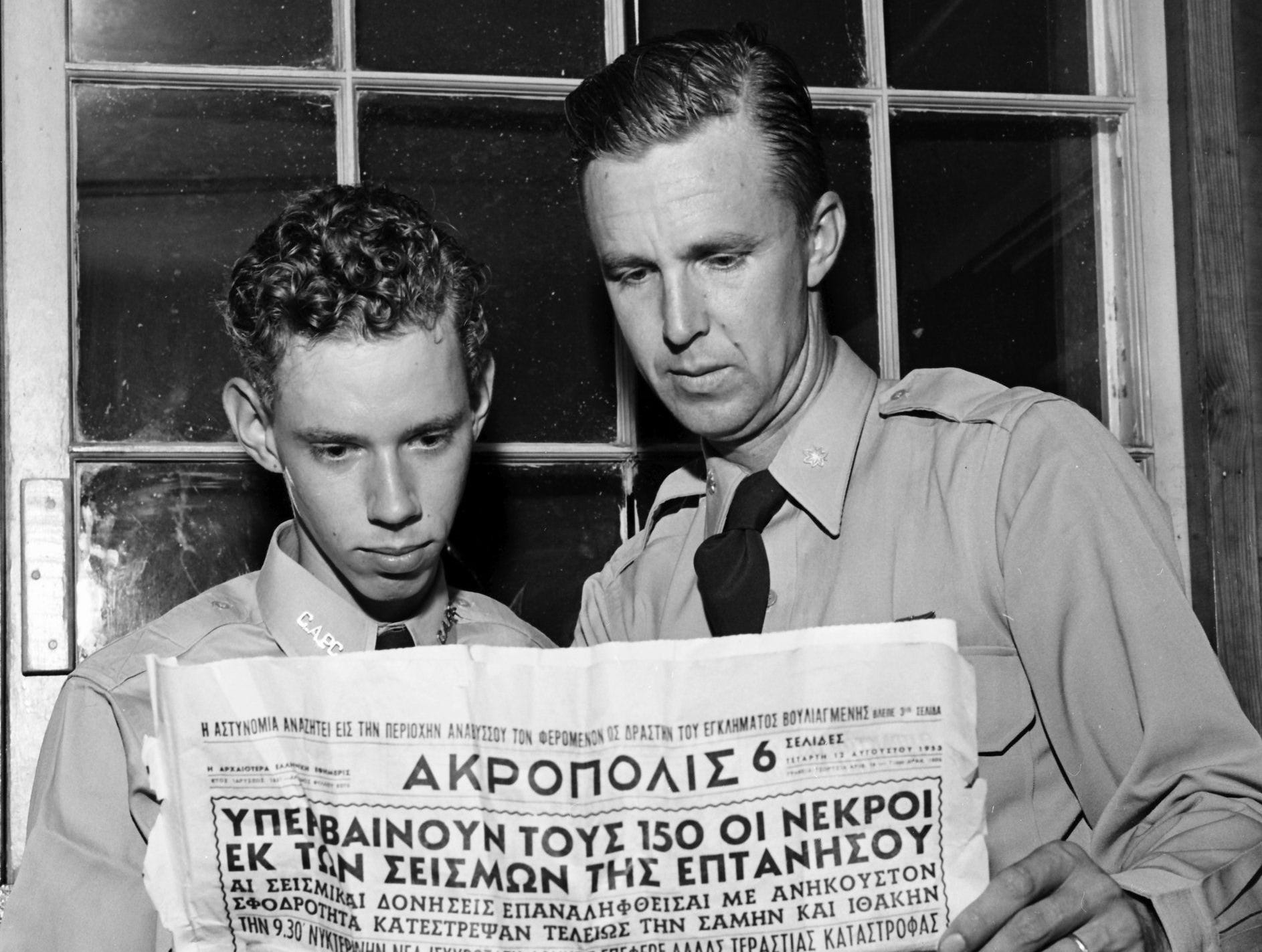 Pictures in a Greek newspaper recall to Maj. Eugene Cook, right, of 4735 Lynn Road the earthquake-battered Ionian Islands of Greece in August 1953. He shows civil Air Patrol Cadet Frank Isele of 1921 Netherwood the scenes he saw while flying low over the isles just as the quake was shaking them. Maj. Cook and young Isele returned recently after a month-long CAP-sponsored tour of Europe.