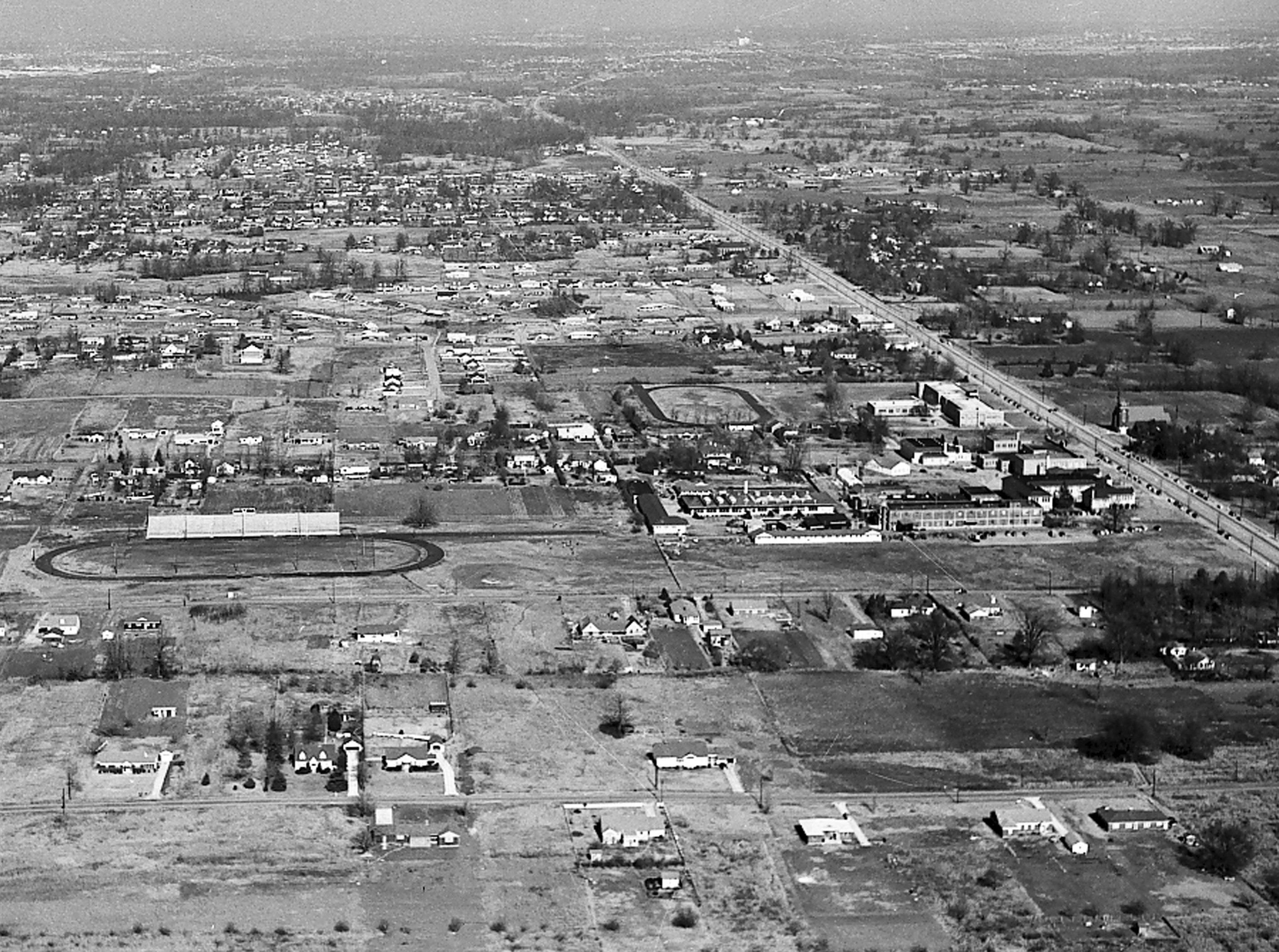 The southern area of Whitehaven is seen in this photograph from July 1953. Palmer Road is visible in the foreground and Elvis Presley Boulevard is running diagonally at right. Whitehaven High School is at extreme right center. The oval at left center is the football stadium behind Whitehaven High School. Whitehaven Baptist Church is seen at far right center. The photograph is taken looking toward the north.