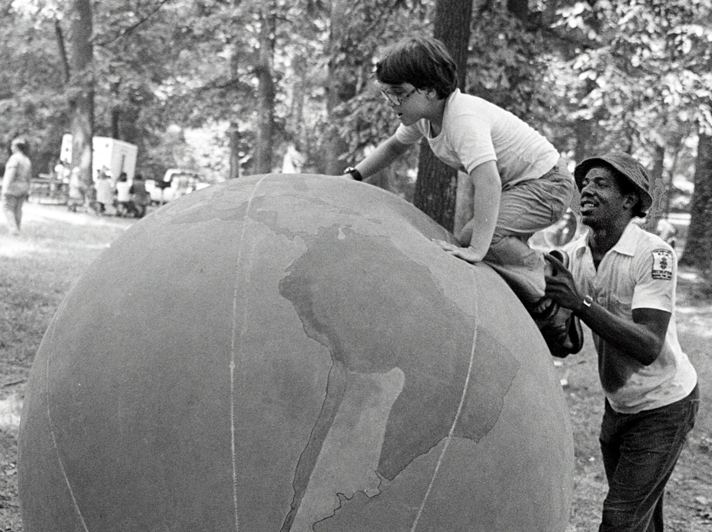 Ten-year-old Yvette Golden of the Baptist Children's Home got a boost to the top of an earth ball from Park Commission staff member Randy Jones at the Overton Park picnic area on 8 Aug 1979.  The Park Commission provided games, puppet shows and other activities yesterday for about 200 youngsters from orphanages in the Memphis area during the 18th annual Orphans Picnic, sponsored by the Jaycees.