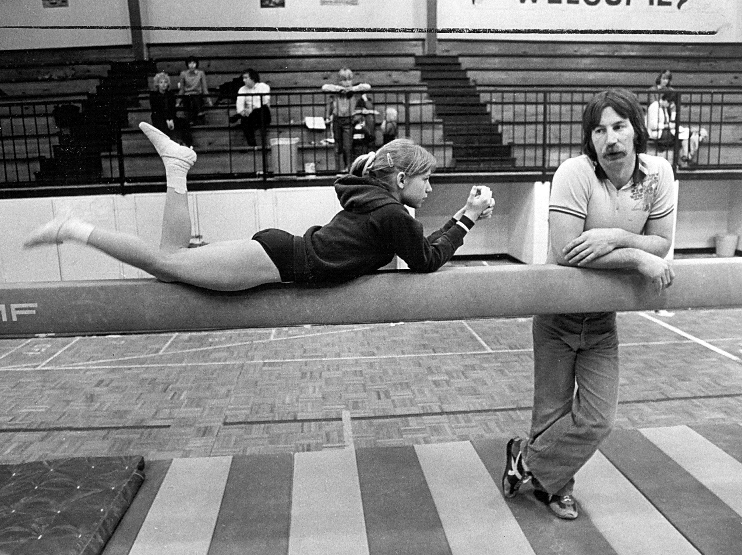 Gymnist Lucy Wener takes a break on the balance beam and relaxes with coach David Neel on 19 Mar 1981.