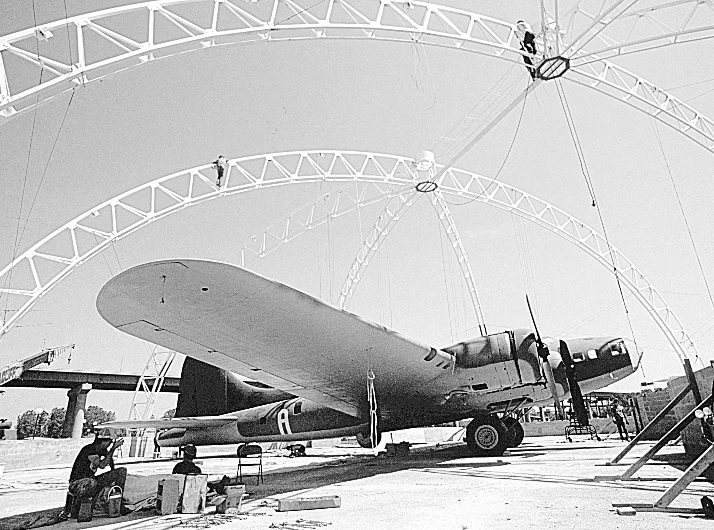 Workmen eat lunch in the shade of the Memphis Belle's wing on 21 Apr 1987 while others erect the dome frame of the new hangar housing the World War II B17 bomber at Mud Island. The fabric covering for the dome is scheduled for installation later in the day. The dome, located at the north end of Mud Island river park, was built after a fund-raising campaign last year saved the plane from being reclaimed by the Air Force. Dedication of the building is scheduled for May 17.