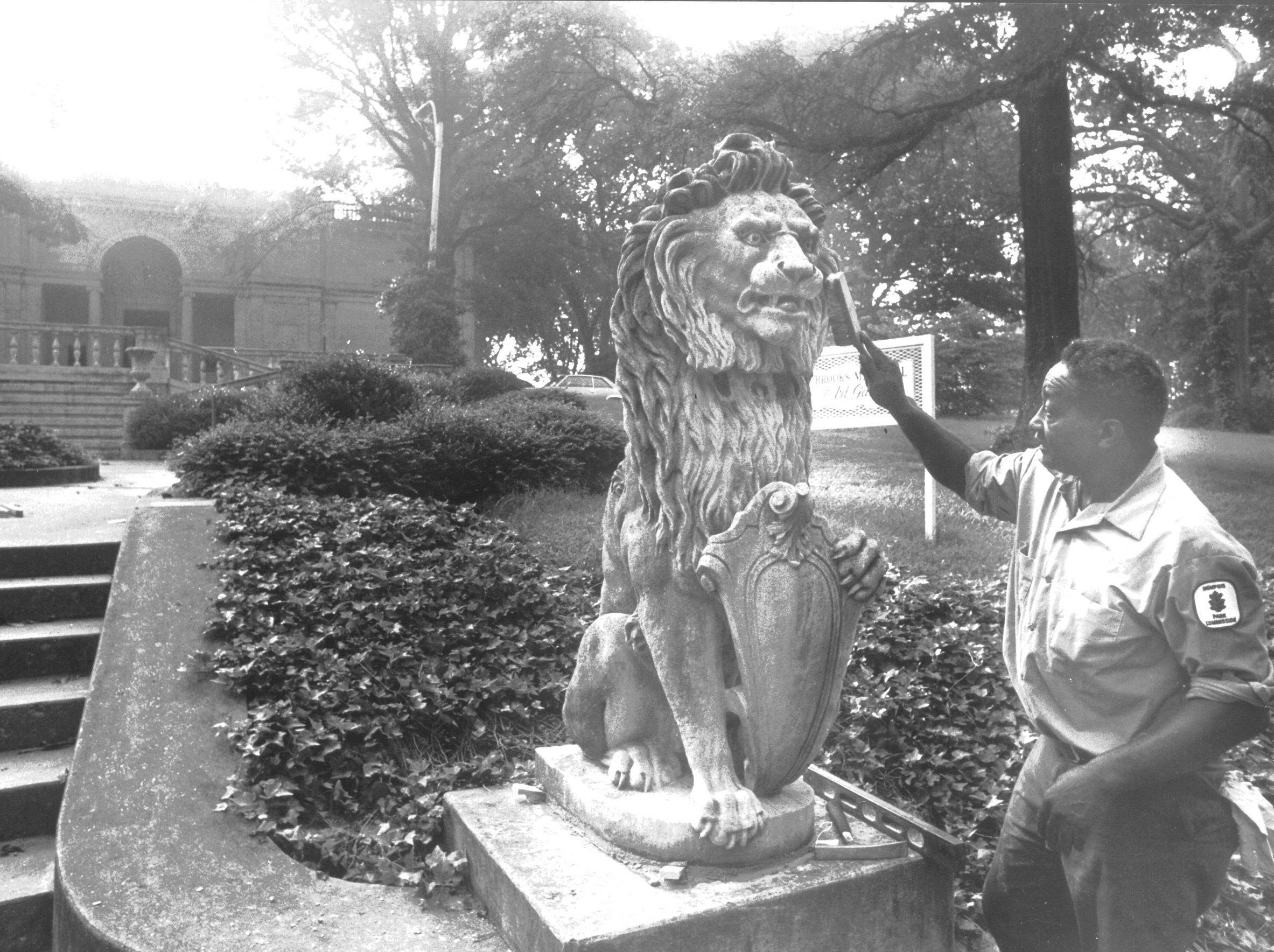 Memphis Park Commission employee Harden Bryant dusts off one of the two lions from the demolished Hill mansion on Union Avenue that have been donated to Brooks Memorial Art Gallery in Overton Park on Sept. 5, 1979.