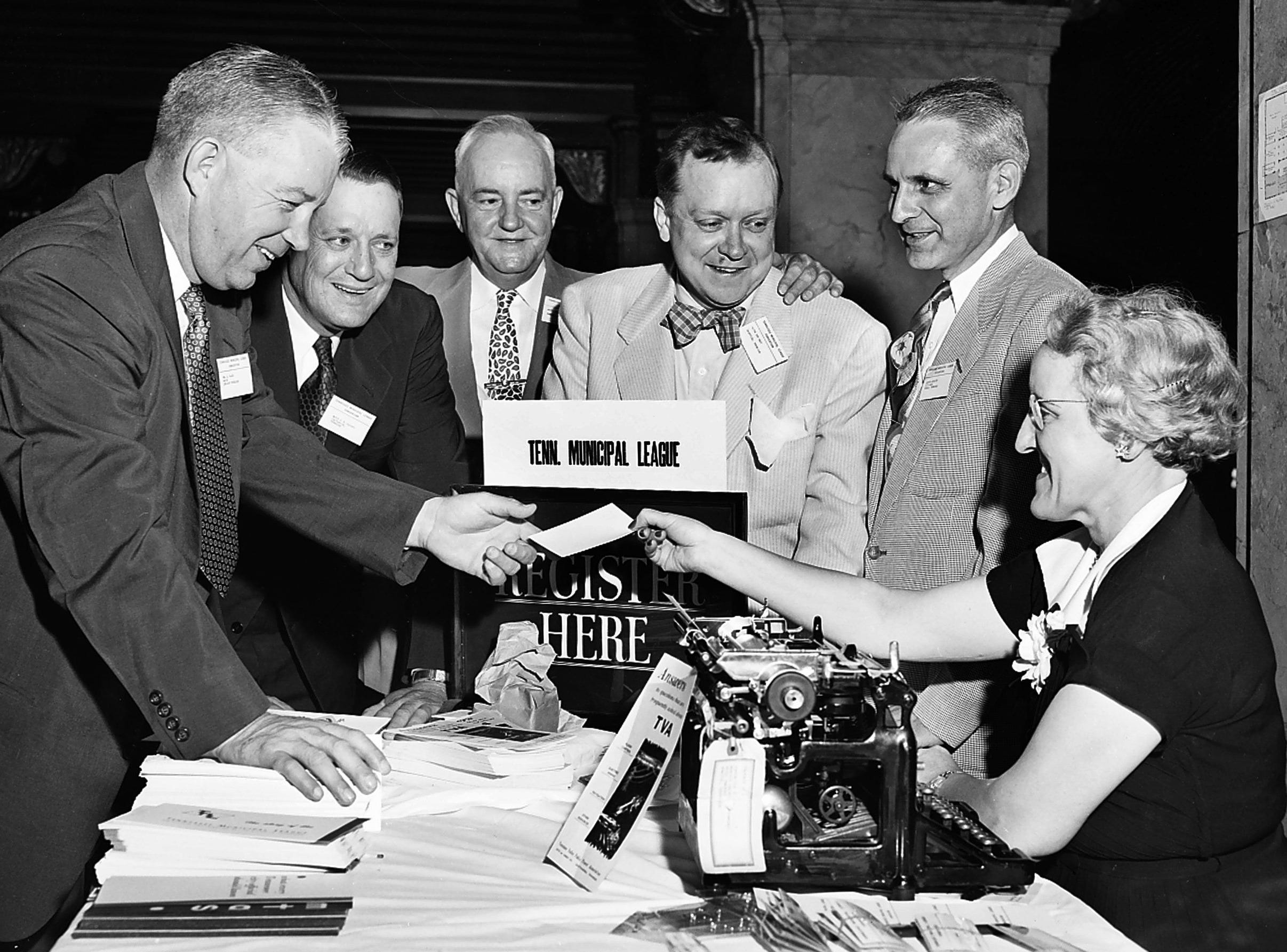 The reception desk at the Peabody was a busy place on 7 Jun 1953 as top officials from all over the state registered for the annual Tennessee Municipal League meeting. Mayor Frank Tobey, third left, of Memphis was host. Others are, from left, Mayor W.D. Baird of Lebanon, TML president; Mayor P.R. Olgiati of Chattanooga; Mayor Ben West of Nashville; Armond Arnurius of Norris, city recorder; and Mrs. Joe Dixon of Nashville, TML secretary.