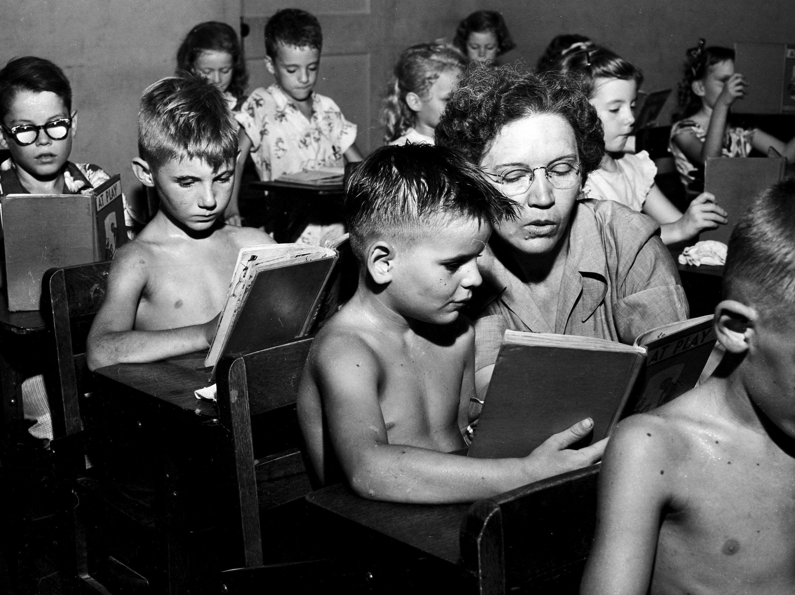 Overcrowded and overheated are the prevailing conditions at Frayser Grammar School on 31 Aug 1951. Almost 700 first, second and third graders are finding little elbow room. Miss Marie Watkins, second-grade teacher, offers assistance to Billy Sigler, 7, son of Mr. and Mrs. W.L. Sigler of 1383 Quinby, as Dwight McClain, also 7, of 3093 Signal, waits his turn. And the temperature was hovering at 105 degrees.