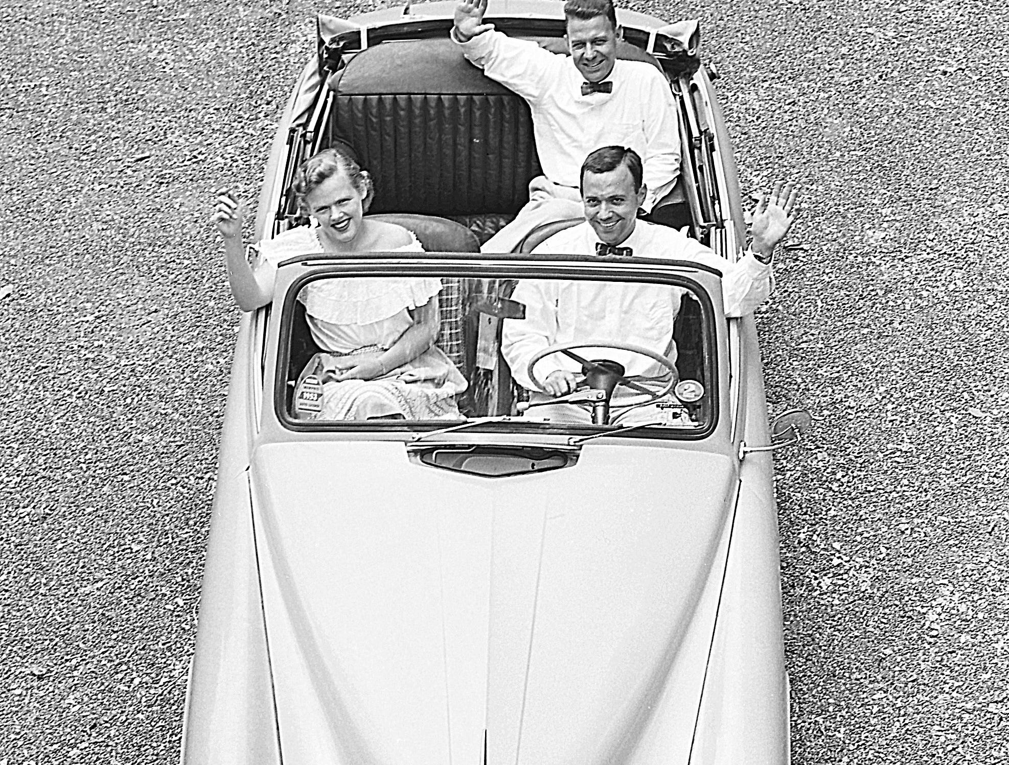 A bird's-eye view of three foreign car enthusiasts shows Mr. and Mrs. Edward Dewey (Front Seat) of 46 Morningside Park and his brother, William C. Dewey of 48 South Bingham, in Ed Dewey's Hillman-Minx in September 1953.  The Dewey brothers were among the first foreign car owners in Memphis, bringing home a Morris in which they had toured Europe.  Now, each brother owns a Hillman-Minx.  The small cars are easy to handle in traffic and to park.