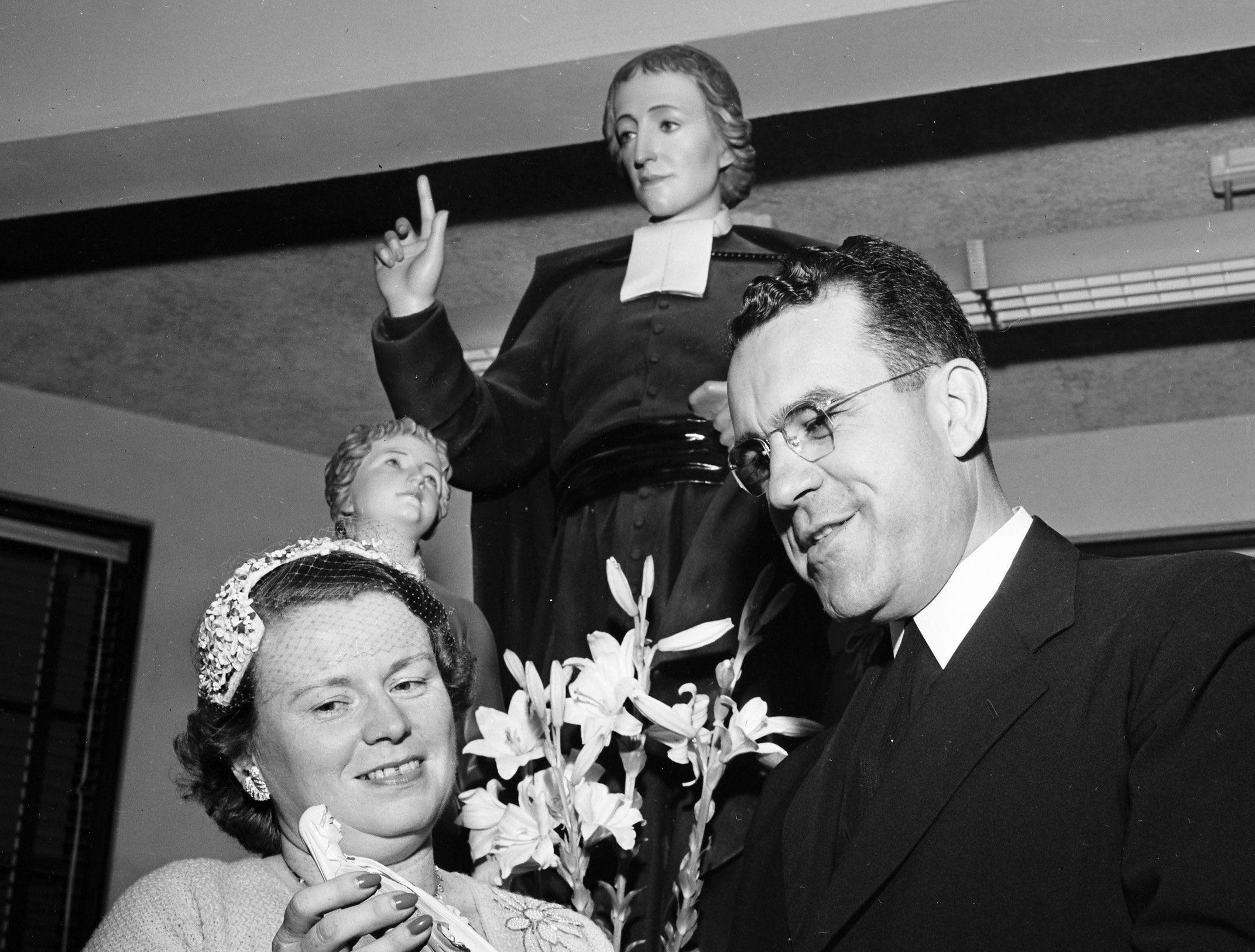 Brother H. Richard, retiring director of Christian Brothers College who served the maximum six-year term permitted by his order, was honored at a farewell reception in May 1953. Mrs. David Saxon, president of the CBC Mothers Club, presented him a small statue of the Virgin to take with him. A larger statue of the Virgin soon will be installed at the school in his honor. The statue in the background is of St. John Baptist de la Salle, founder of the Christian Brothers order.