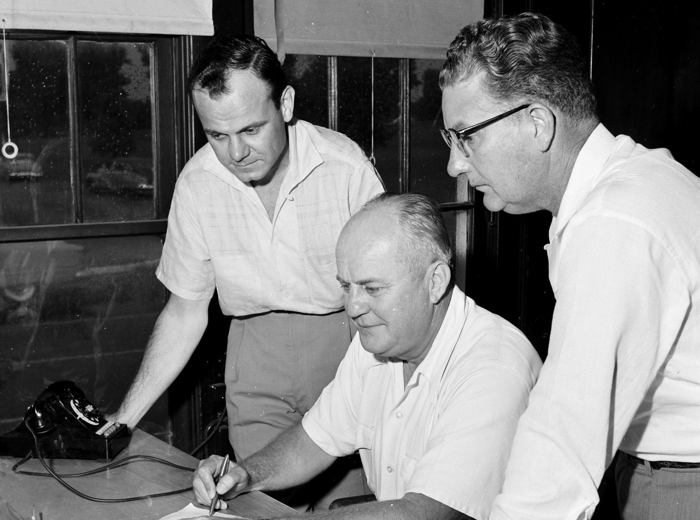 P.A. Gates Jr., center, president of Gates Lumber Co., talks over the sale of the company with R.F. Sharp Jr., left, secretary and assistant treasurer of North Memphis Lumber Co., and Max Pinkerton, North Memphis president, which purchased the company. The sale took place in July 1955.