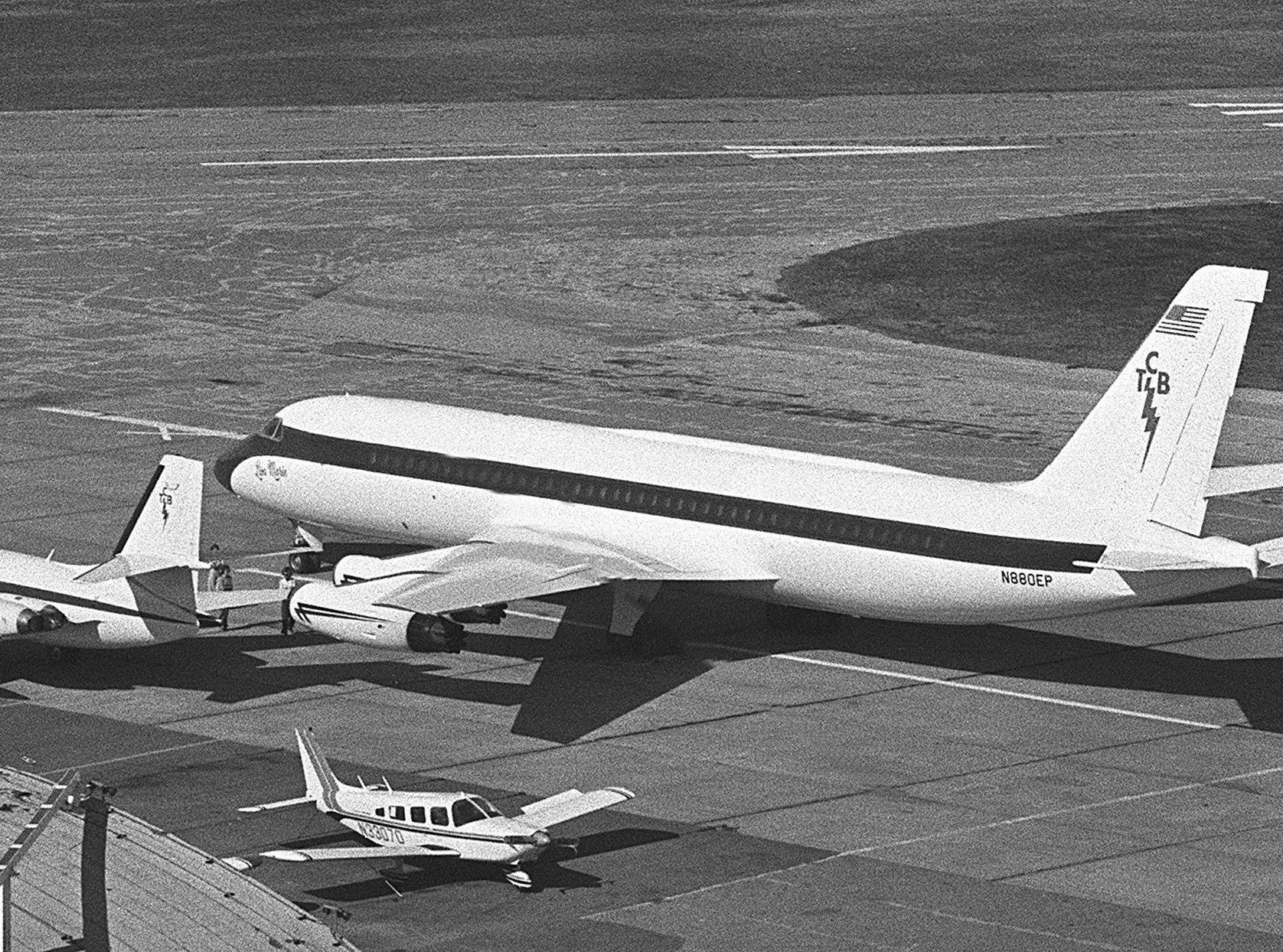 """The Lisa Marie, newest craft in Elvis Presley's small air fleet, is at Memphis International Airport on 12 Nov 1975 getting final touches before being put to use for touring. The converted Convair 880, formerly used by Delta Air Lines, is named for the entertainer's daughter. It was bought for $1 million and it took another $750,000 to fix it to his taste in Forth Worth, TX. While not as elaborate as some reports have had it, the plane should be quite comfortable for the Memphian and his personal crew. It has a galley with stove, refrigerator and coffee maker, a private bedroom with queen-size bed, a dining room with eight chairs, two sitting rooms, two bathrooms with gold-plated fixtures and a shower in one, plus 29 seats for passengers. It requires a pilot, copilot, flight engineer and stewardess. Elvis also will keep the Lockheed Jetstar (smaller plane at left), a 9-seater, for touring purposes. On tours, he will need to lease a third plane for back-up groups, equipment and wardrobes. He has two other jet planes on the market. The small propeller plane in photograph is not part of his """"air force."""""""