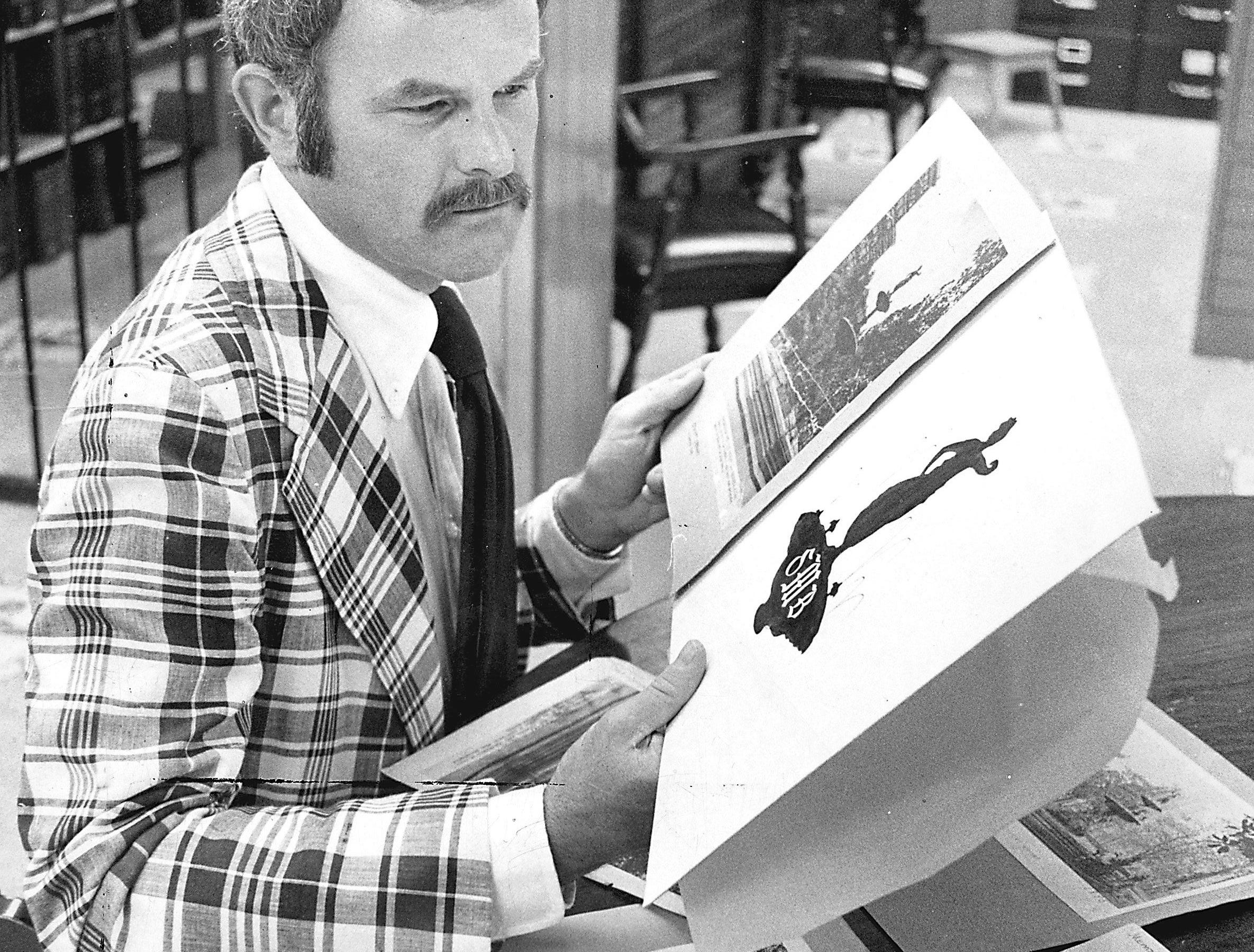 Robert Ruffin III looks over photographs of Hebe, the star adornment of the Court Square fountain, in August 1974. From the photographs, he was able to design the logo which will appear on the stationery, invitations and program for the Symphony Ball, one of Memphis? most illustrious annual benefit events. The ball is scheduled for Oct. 5 at the Germantown home of J. Everett Norfleet.