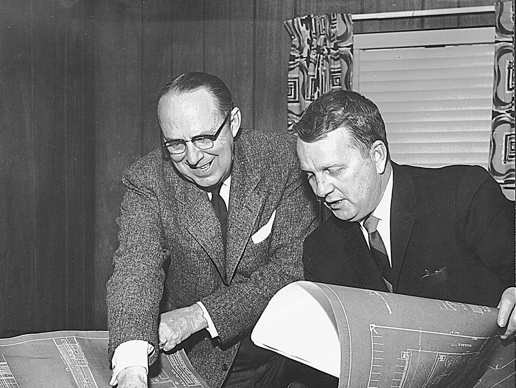 Wallace E. Johnson (left), president and Kemmons Wilson, chairman of the board of Holiday Inns of America, Inc. look over plans for a new project in July of 1958.