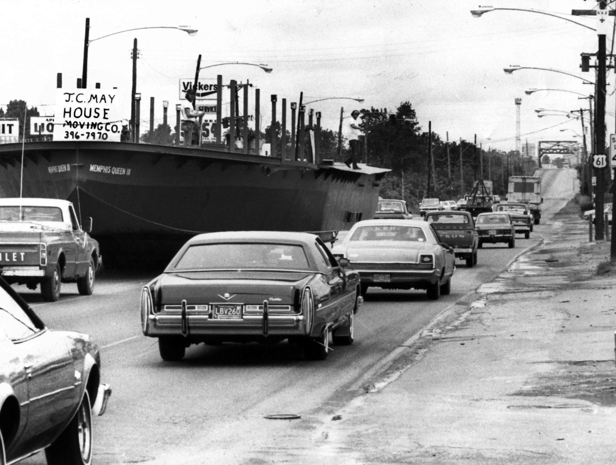 """The hull of the Memphis Queen III, hatched in the back yard of former """"fleet"""" owner Tom Menaley, cruised majestically but slowly down U.S. 61 toward McKellar Lake on 17 Aug 1977. Meanley started construciton in November, 1975, in """"my shipyard,"""" which is an old barnyard at 1398 West Shelby Drive. When finished, the new Queen will be 114 feet long, 35 feet wide and will carry a maximum of 400 persons on 500 square feet of deck space. Said Meanley, who is in the process of selling the Memphis Queen Co. to his son, """"It is designed in the tradition of old steamboats, but will have a functional paddlewheel, one that will actually help in pushing the vessel. It also will have two screw propellers, each with a separate engine."""" The moving trip was 'quite uneventful' with the hull resting on steel beams like a house. It traveled at 15 to 20 mph. It will be launched, then go to drydock for attachment of cabins, decks and other things needed by excursion steamers."""