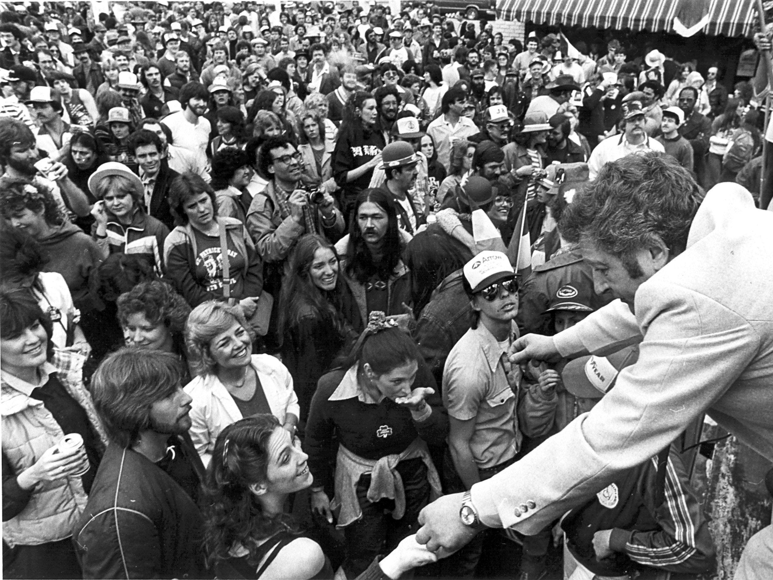 Visiting Irish matchmaker Jimmy White (Far Right) passes out Shamrocks to the huge crowd participating in the St. Patrick's Day Pub Crawl on 17 Mar 1982.