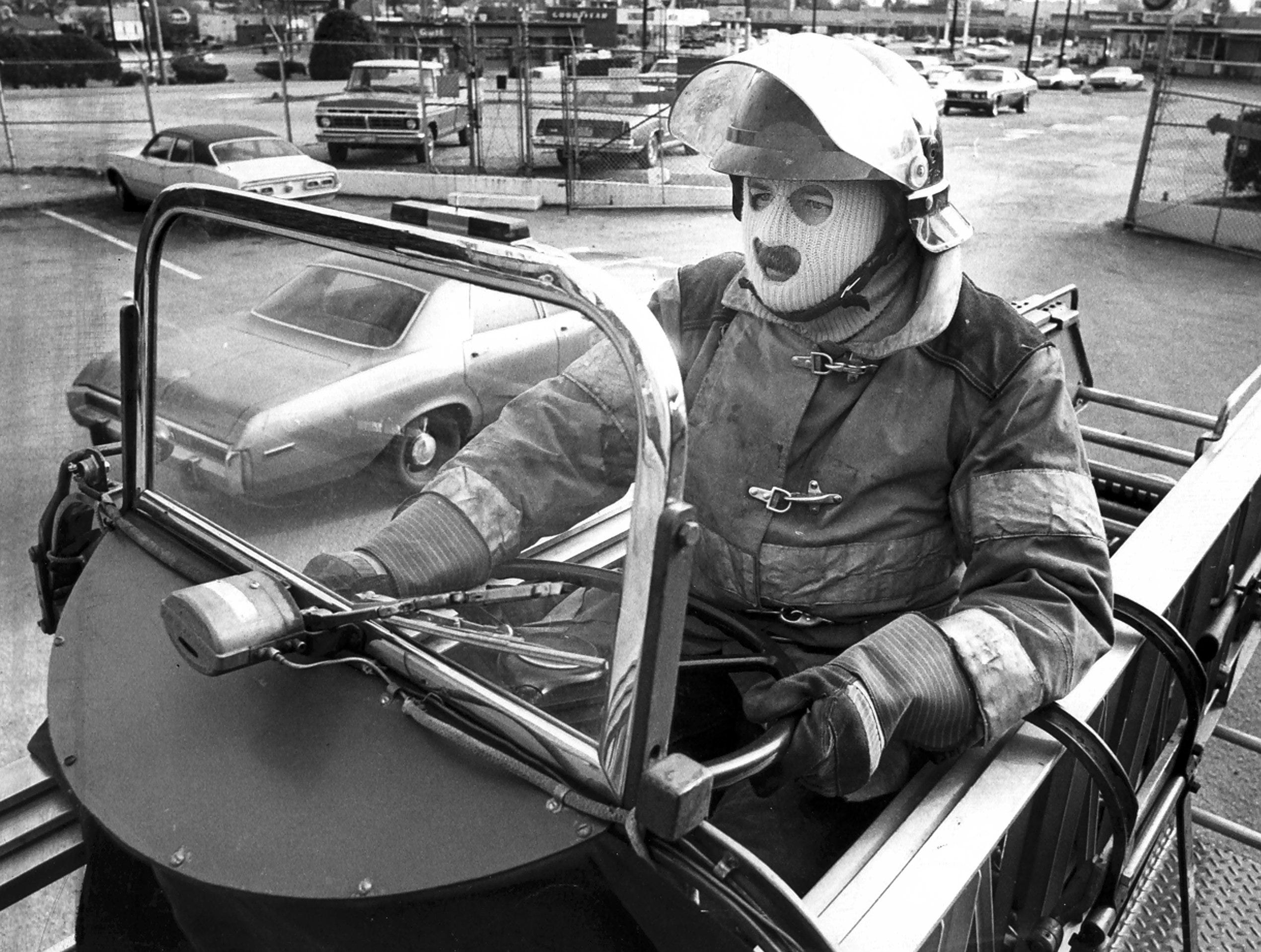 """January 18, 1977 - Memphis fireman Robert Pleasant, the tillerman on aerial turck #7, has to wear a ski mask in his """"convertibe"""" cockpit on the back of a 100 foot long aerial truck on Jan. 18, 1977. Pleasant says he sometimes has icicles on his mustache."""