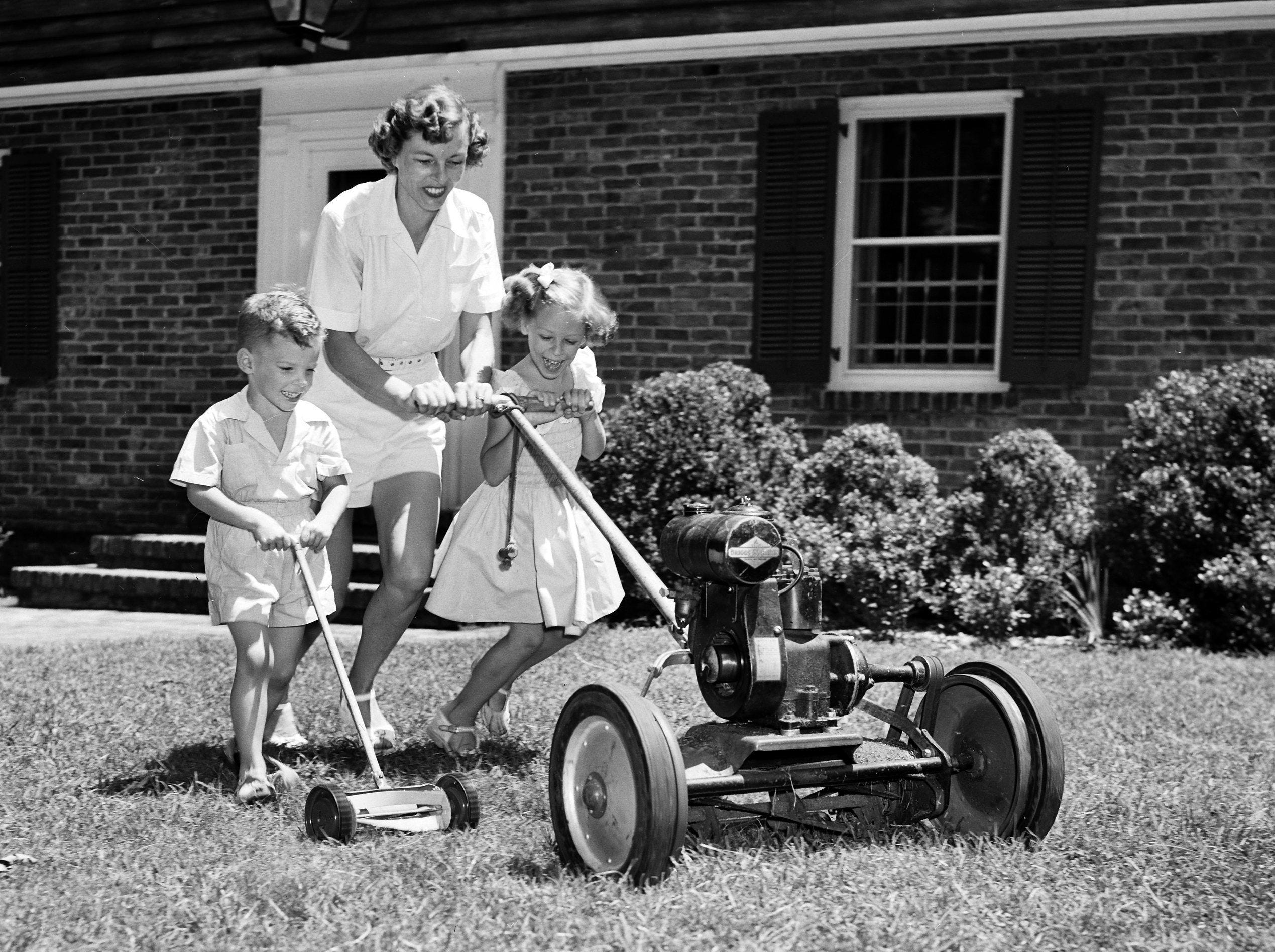 Mowing the lawn can be fun ? especially with a high-powered mower and two eager young assistants. Showing how a trio can accomplish the task quickly on 10 Aug 1951 is Mrs. Charles B. Dudley Jr., who guides the machine with her daughter, Mary, on the lawn of their home at 710 South Perkins. Cutting a path of his own is her son, Chip.