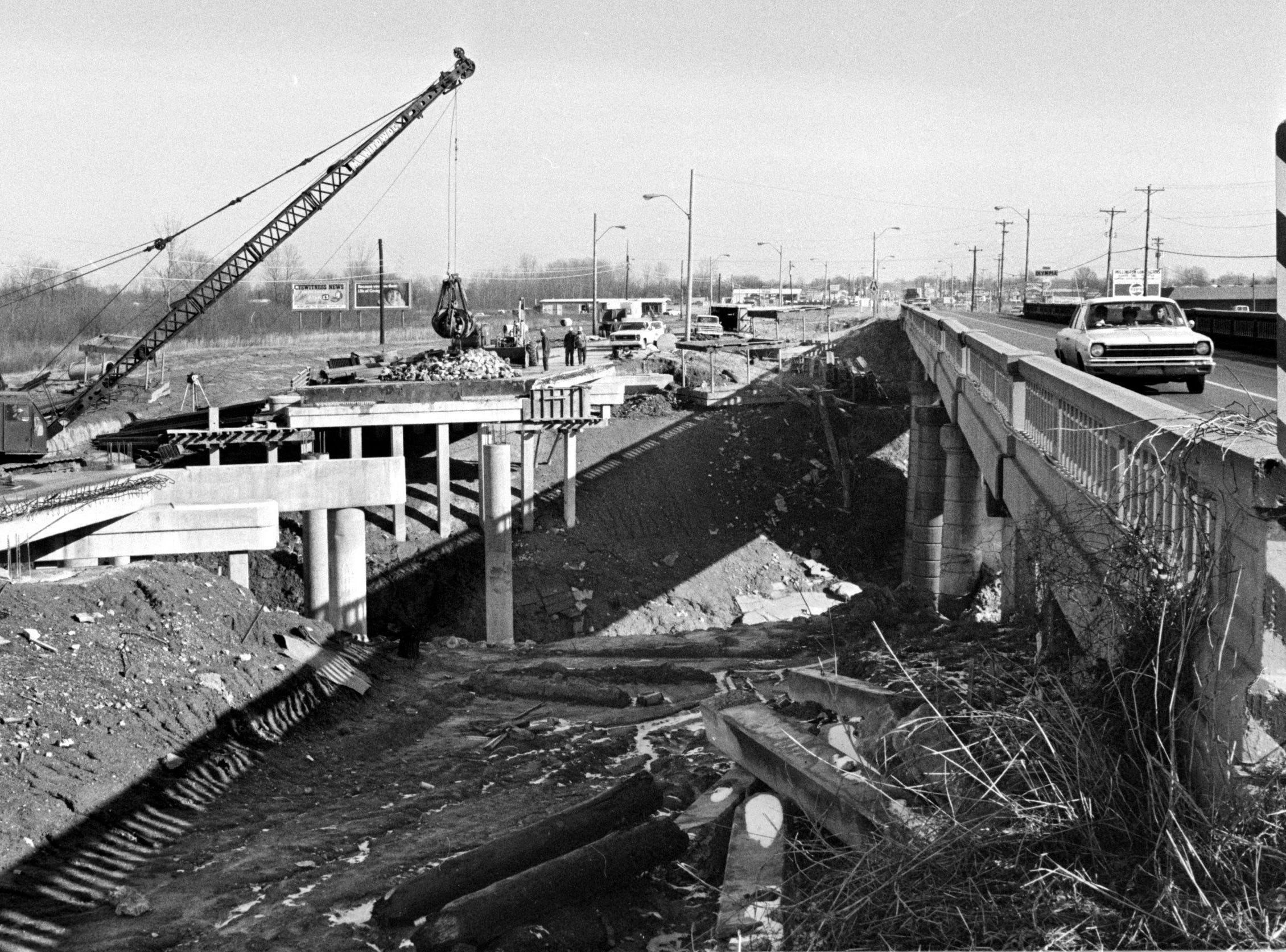 Work progresses in January 1975 on a two-step bridge project over Big Creek south of Millington that will smooth the flow of traffic in and out of the county's navy town. The narrow, old bridge was being undermined by Big Creek and was otherwise deteriorating. Workers are widening the southbound bridge from 24 to 42 feet and are aiming at a May 1 completion date. The northbound section will be replaced with a 42-foot wide span, hopefully by Dec.1. Cost of the project , including work on embankments and culverts is $960,507.38.