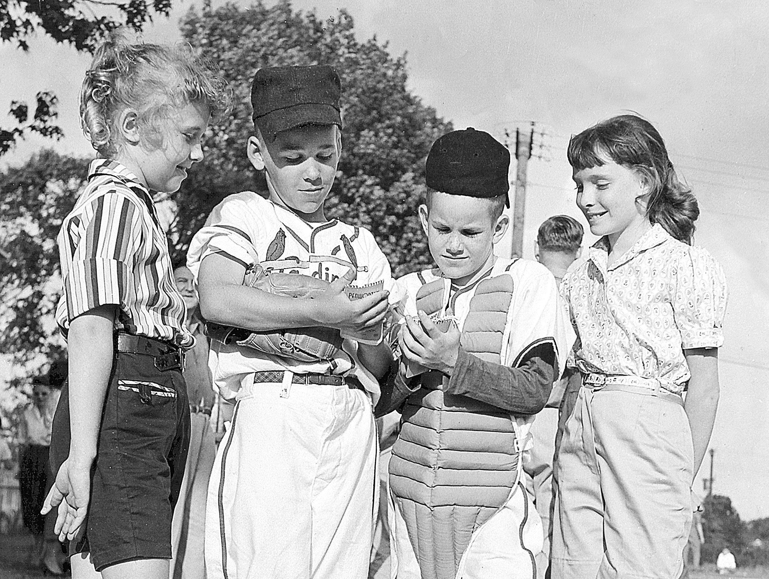 Hero worshiping fans get autographs from two stars on the St. Louis Pee Wee team in the Knights of Columbus League in the summer of 1958. At left, Lynn Zanone, 9, of 4972 Devonshire and Kris Mitchell, 11, of 4724 Barfield Road, right, found pitcher Jon Hardy, 10, of 5429 Shady Grove Terrace and catcher Dwight Morris, 9, of 5479 North Suggs ready to sign. St. Louis was preparing for a game with Immaculate Conception.