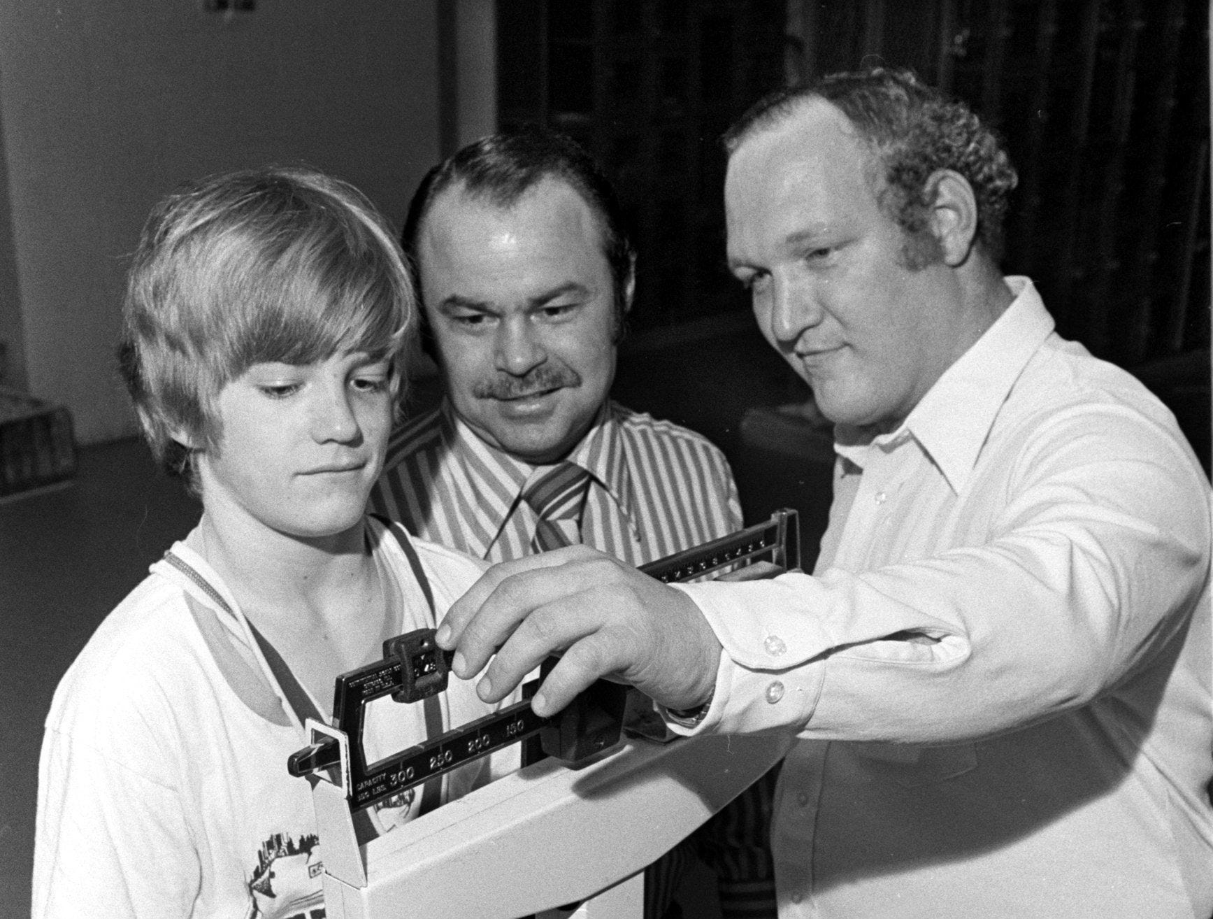 Bishop Byrne wrestler David James is weighed at 98 pounds by his coach Carlo Prani (Center) and Larry Giannini in Jan 1975. The Red Knights are preparing to enter the HIllsboro Invitational Tournament in Nashville, along with Raleigh-Egypt and Germantown.