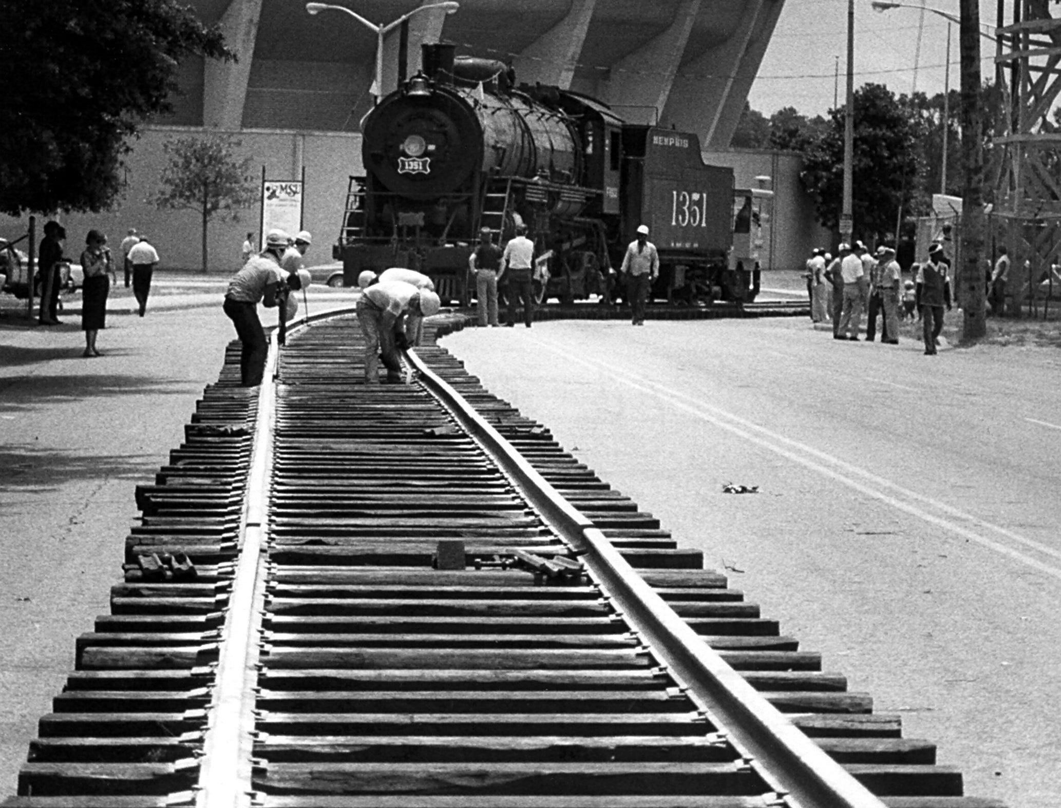 It's a heck of a way to run a railroad, but workmen have little choice while moving the 1912 Frisco locomotive past the Mid-South Coliseum on 30 Jul 1983. Track panels were leap-frogged around the 150-ton engine, displayed at the fairgrounds for 31 years. The engine was towed toward Southern Railway yards and eventually will be moved to a shop for restoration before a trip to next year's World's Fair in New Orleans.