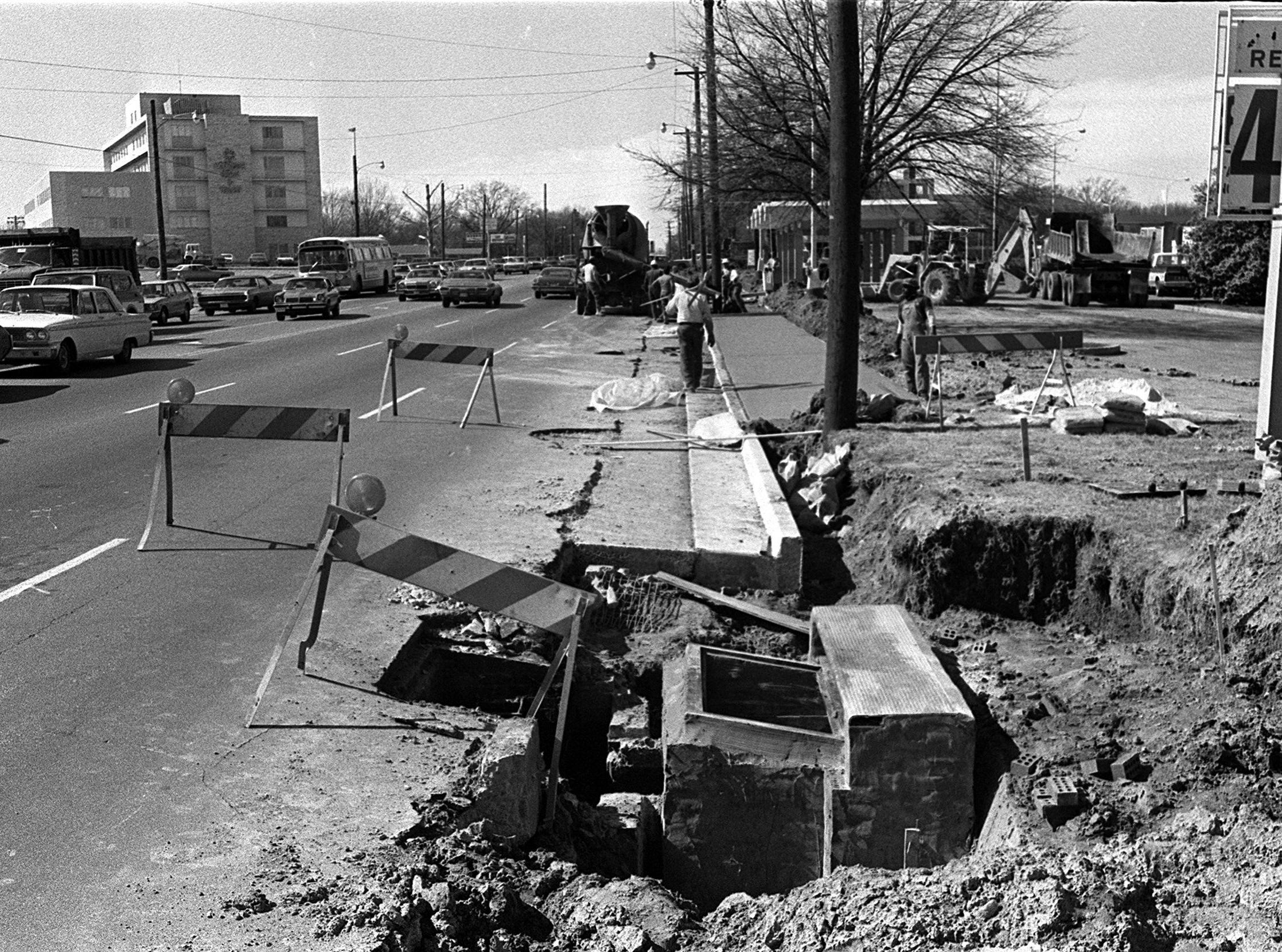 Curb and gutter work is being completed as Poplar Avenue is widened west of Perkins Extended on 28 Feb 1975. This photograph, looking to the west near Perkins Extended indicates that Sears, Roebuck and Company is selling regular gasoline for 48.9 cents per gallon.