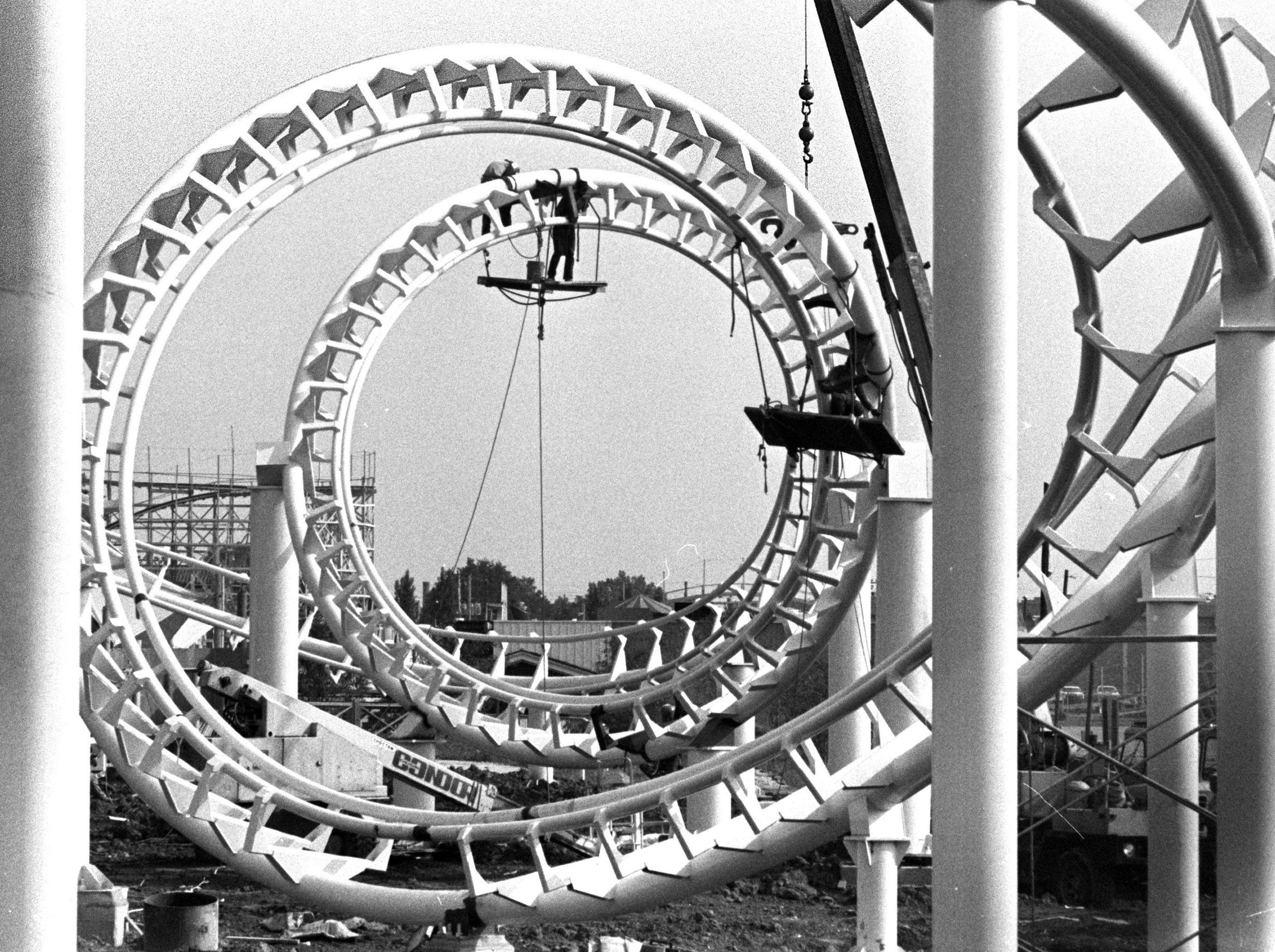 """Workmen have begun the monumental task of painting """"The Revolution"""", Libertyland's newest ride on 10 May 1979. Libertyland officials expect the $1.7-million loop-corkscrew ride to be in operation in about two weeks. The ride features a 360-degree loop that will turn its riders upside-down and a double corkscrew 'guarnateed to thrill' each of the 28 passengers the ride can carry per trip. The ride will last 80 seconds, travel over 1,565 feet of track and reach an altitude of 95 feet at the loop. It can accommodate about 1,000 persons an hour. Libertyland officials are calling the ride a """"white knuckle senses-scrambler."""" Fred J. Griffith / The Commercial Appeal files."""