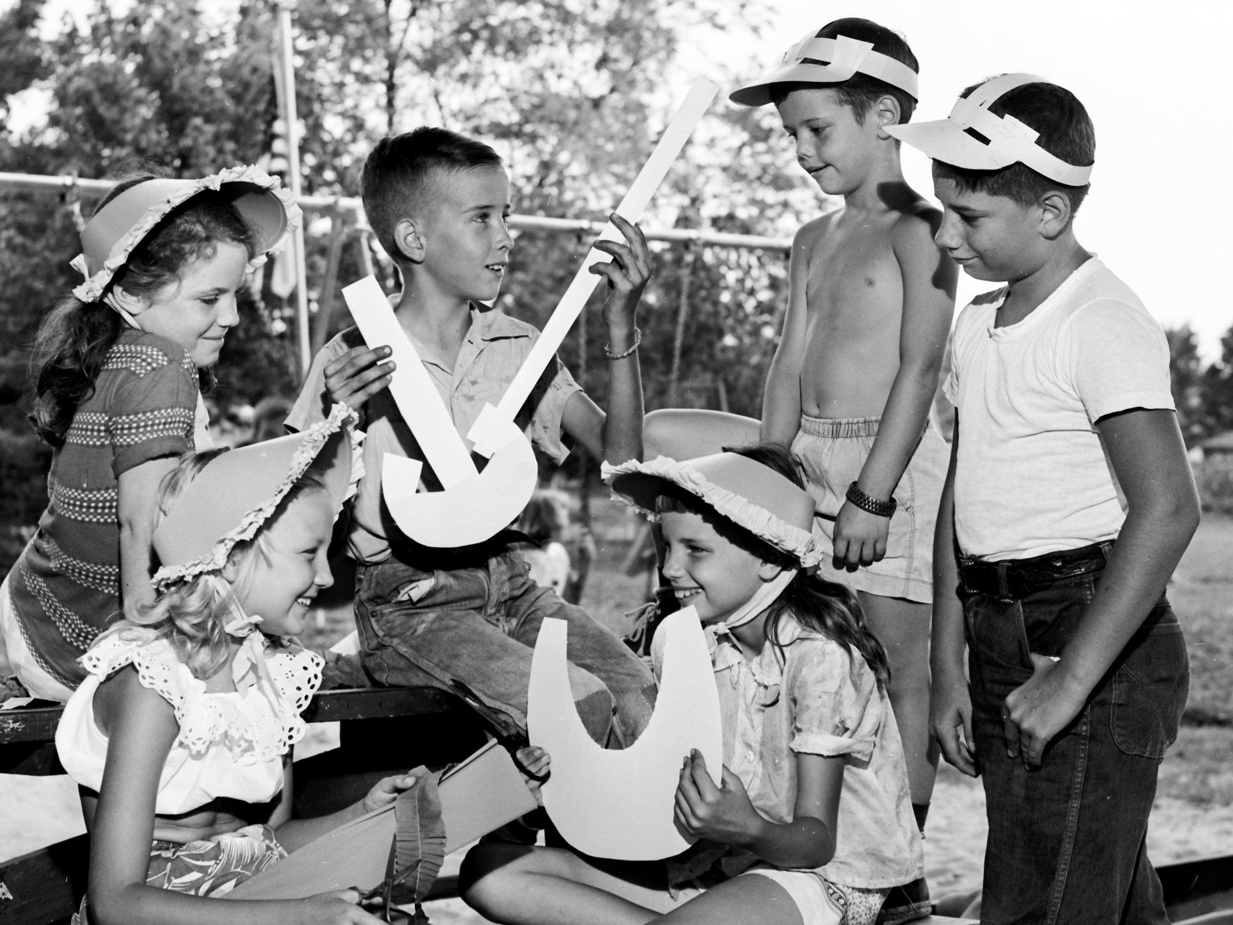 These youngsters at Highland Park Playground are fashioning headgear under the direction of the Recreation Department of the Memphis Park Commission in August 1953. Myra Todd (Seated Left) 10, of 3519 Mayflower, wears a cardboard sunbonnet and holds crepe paper and scissors to make the ruffles on the bonnet held by Joyce Ann Joyner (Seated Right), 9, of 1399 National. Meanwhile (From Left at Back), Rosemary Jones, 10, of 3538 Mayflower watches as Buddy Joyner, 11, of 1399 National demonstrates how to make a boy's sun visor like the one worn by Don Childress, 6, of 3432 Vernon and Jimmy Russell, 14, of 3525 Kallaher.