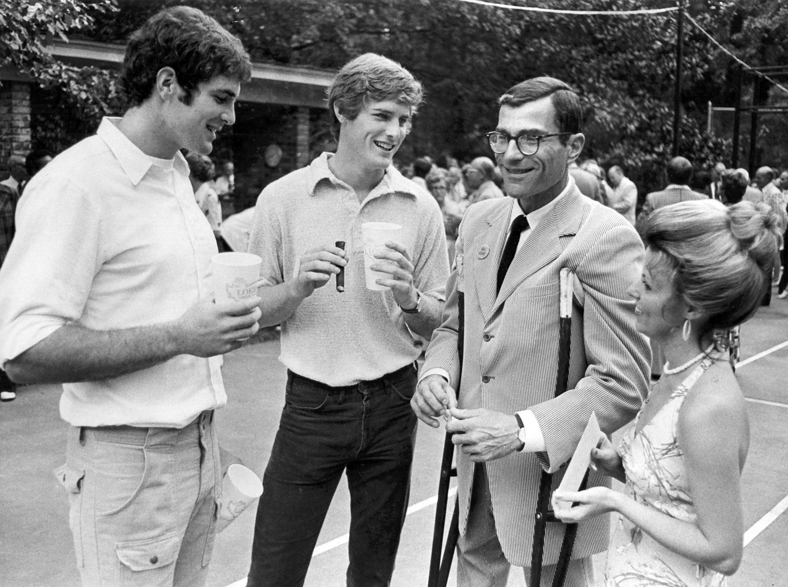From left, Louis Loeb and Bob Loeb join their father Bill Loeb, and Miss Karen Ellis on 8 Aug 1975 to help celebrate the elder Loeb's 52nd birthday. About 2,000 people were invited to the party, held on the tennis courts at the Loeb home on Central Avenue.
