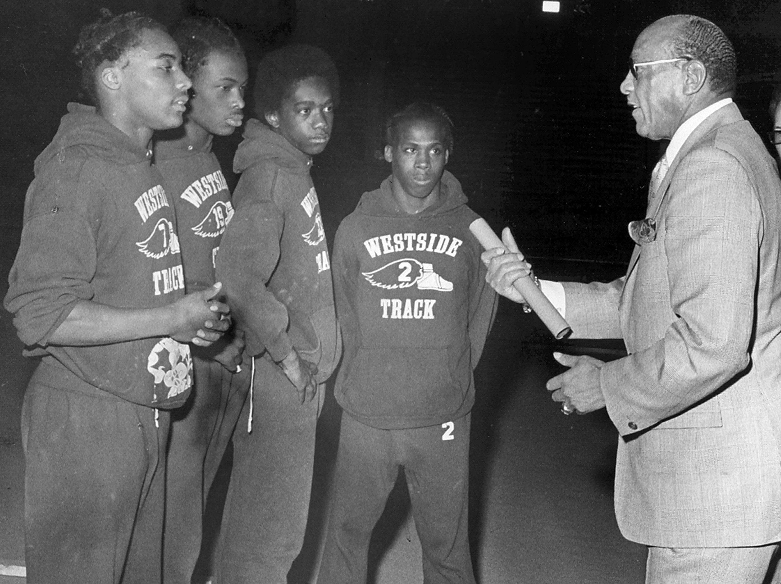 Jessie Owens (Right) discusses track with Westside High School team members (From Left) Michael Jones, Barry Hester, Donald Gray and Lee Caraway in January 1976. Owens captured four gold medals at the 1936 Olympics in Berlin and is still as much a symbol of the Olympics to most Americans an any athlete since Jim Thorpe, tirelessly touring the country on fund raising tours for the Olympic team. He's on the road ten months each year.