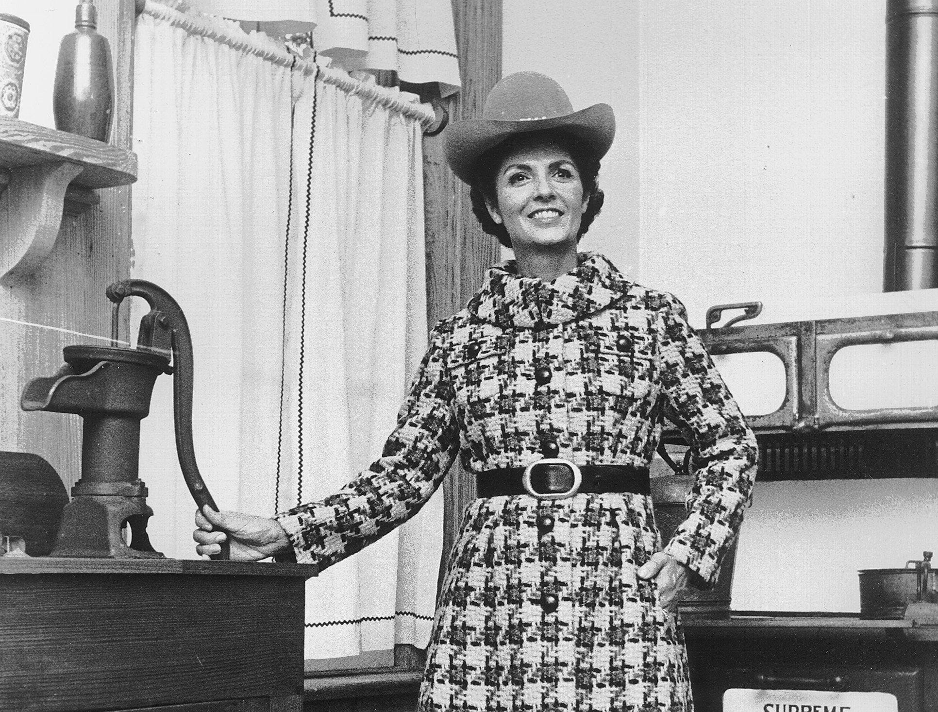 Davidow executes style with a fine needle. This coat of gold and black Scottish plaid with its dress of black jersey is worn by Mrs. Leonard D. Pierotti at the Fontaine House on Sept. 4, 1970. The costume will be shown at Phil A. Halle during Memphis Fashion Week.
