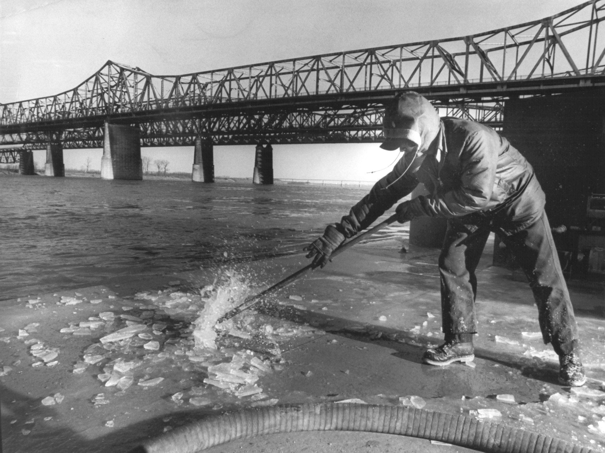 Cecil Starnes of Munford, TN chips ice off the deck of the fuel/water barge at Economy Boat Store at the foot of Illinois Avenue, just south of the Memphis & Arkansas Bridge on 9 Jan 1978.
