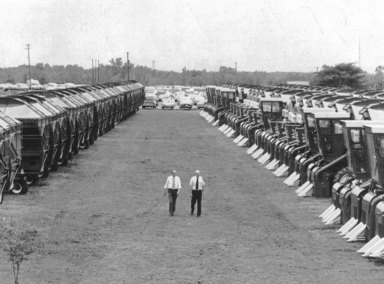 J.R. Massey (Left), public relations manager and R.E. McLure (Right), plant engineer, walk through rows of two-row cotton pickers fresh off the assembly line at International Harvester on 7 May 1975.