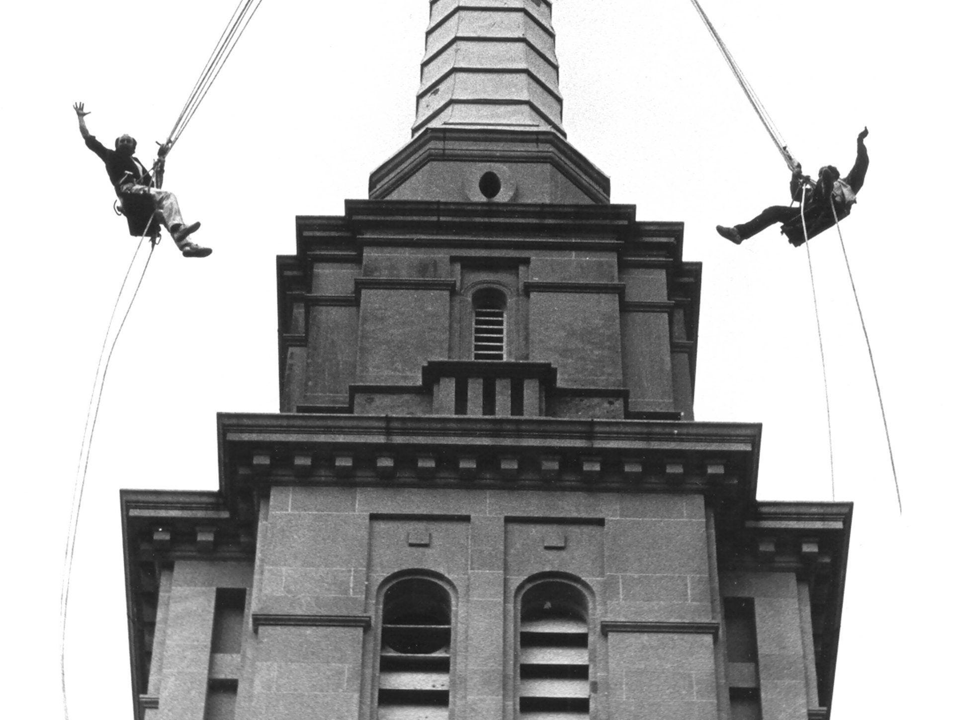 Ron Leecy (Left) and David Pelkey have a high risk job, but manage to have a little fun while doing restoration work on the steeple at Second Presbyterian Church at Poplar and Goodlett on 7 Mar 1987.