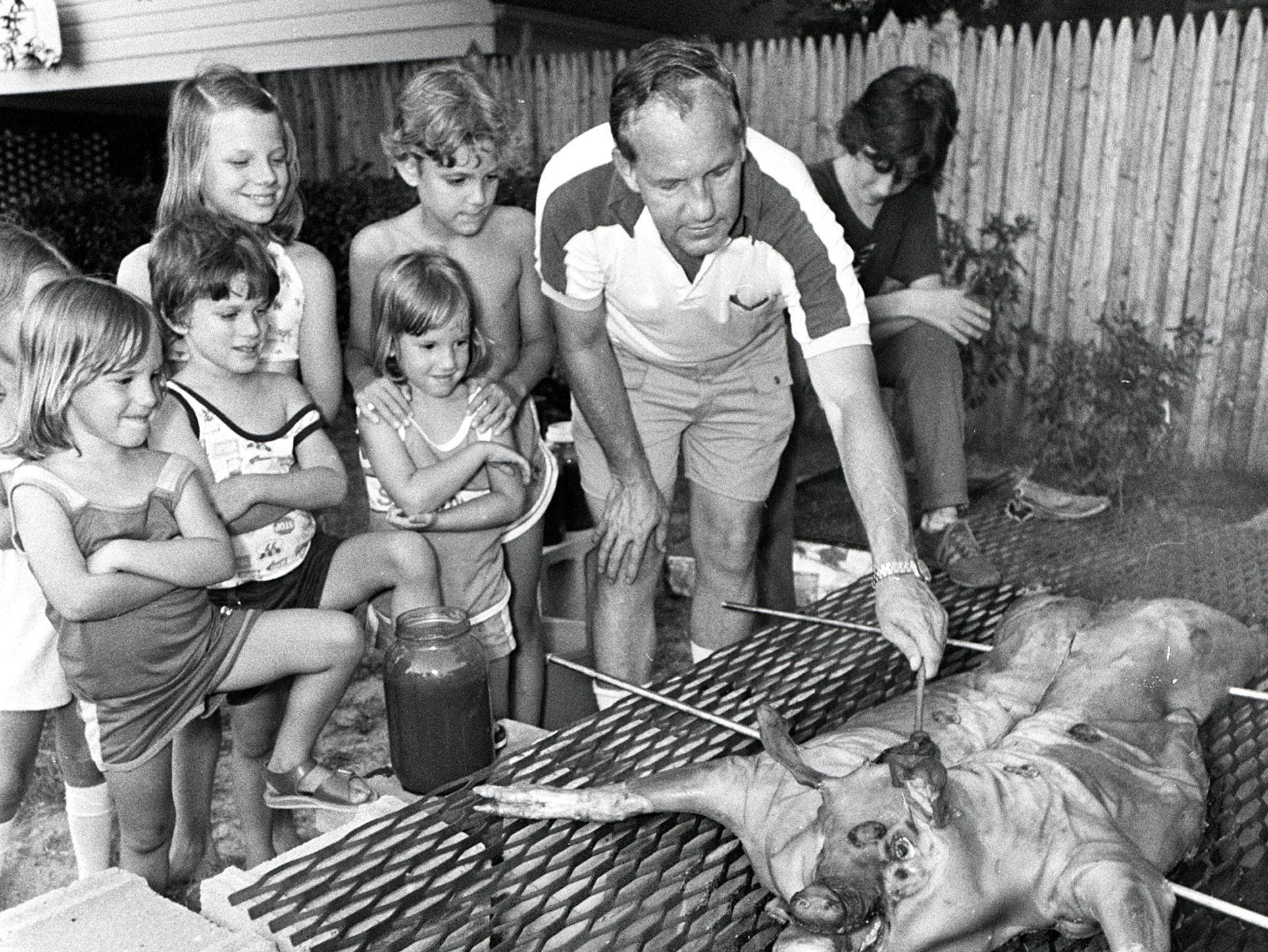 Royce Long of 5343 Keatswood Drive displays for neighborhood children the proper basting touch on 3 Jul 1979 as he prepares a pig for roasting. The pig, which weighed about 100 pounds, will cook for 18 to 24 hours before being served as an Independence Day meal for about 75 people. Royce says it will take 150 pounds of charcoal and four gallons of barbecue sauce before it is finished. Neighbors were to take turns turning and basting the pig overnight. The pit is in the yard of Jerry Todd at 5323 Keatswood Drive.