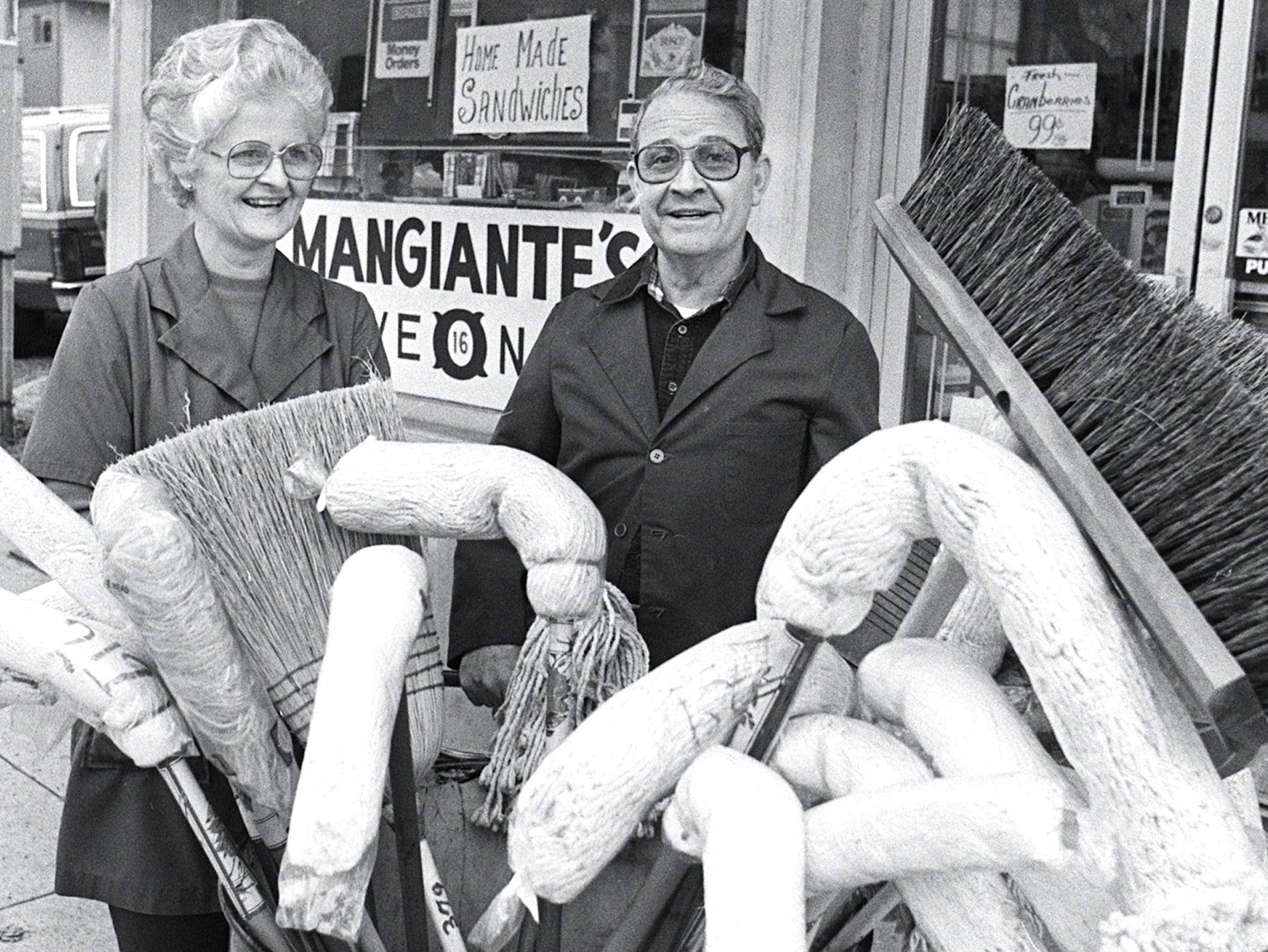 "Margaret and Eugene Mangiante stand behind the broom and mop barrel at their store at 1605 Monroe Avenue on Dec. 26, 1981. Mangiante, 61, the owner of Mangiante's WeOna No. 16, next week will turn over the keys of the neighborhood grocery to new owners. When he does, a 65-year-old tradition will have ended in Midtown. ""I was born upstairs and I've been here ever since,"" Mangiante said. He took over management of the store from his father in 1940 and made no effort to change the store in the 41 years he operated it. Six days a week for 41 years, he has wrestled a metal barrel filled with the brooms and mops to the sidewalk in front of the store, indicating the store was open for another day of business."