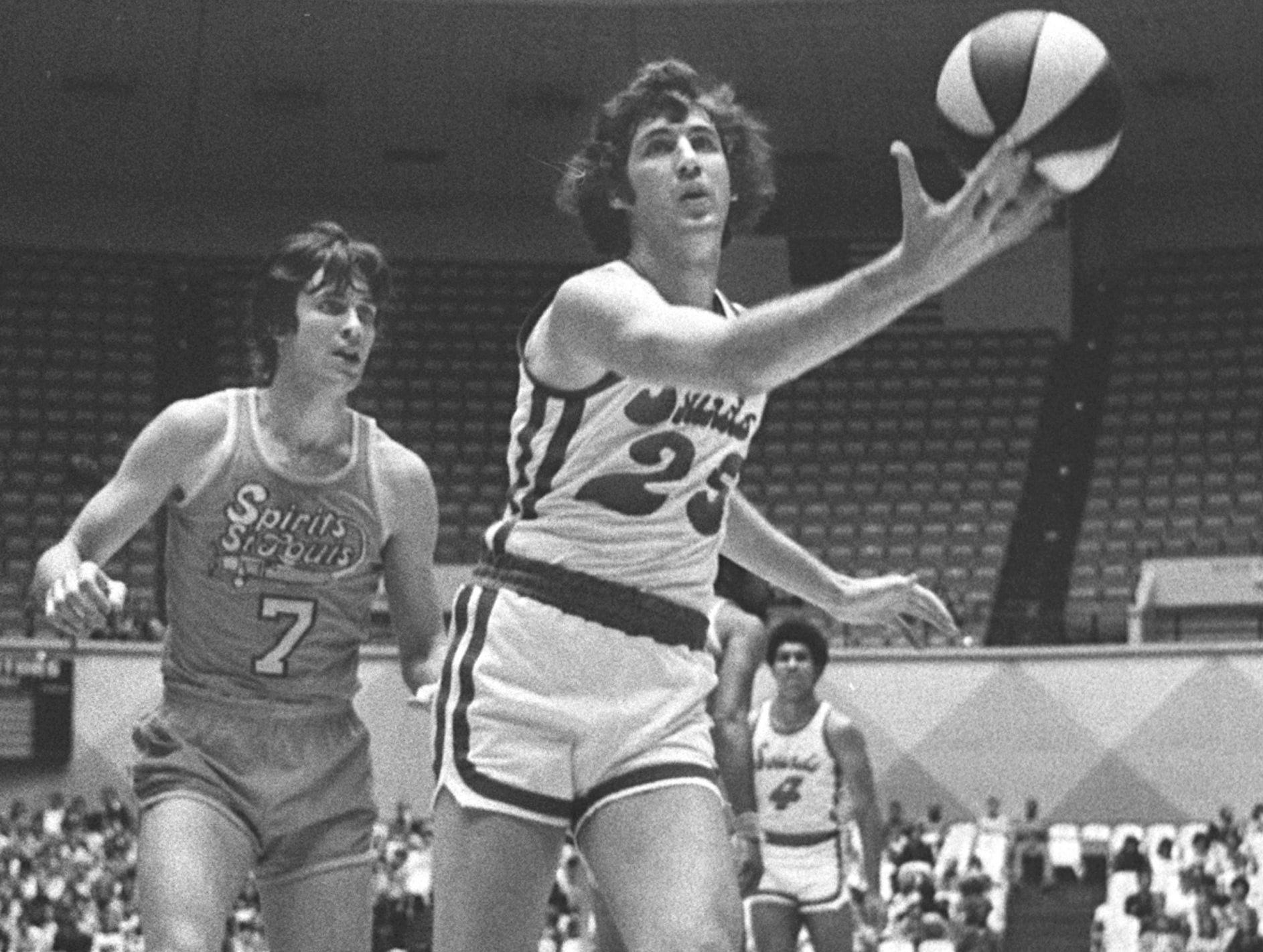 Tom Owens of the Memphis Sounds stretches to snare a pass on 15 Jan 1975 as St. Louis' Terry Driscoll closes in. The Sounds trailed 45 to 42 at halftime and lost 104 to 99 before 2,248 at the Mid-South Coliseum.