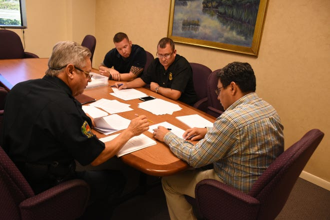 Police Chief Al Schettino, left, and acting City Manager Gil Polanco talk with PBA negotiators on Aug. 28. Union negotiations were supposed to continue on Sept. 10 but a scheduling mishap limited further discussions.