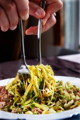 Suitable for the paleo diet, brussels sprouts with Italian sausage is served over zucchini noodles.