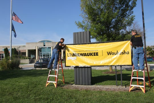 Mike Nicholson (left) and Roger Ulrich secure a temporary vinyl sign into place in front of the UW-Waukesha Commons on Aug. 31 as part of renaming the two-year campus UW-Milwaukee at Waukesha.