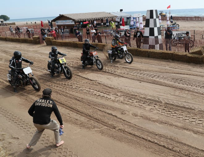 A dropped arm holding a bandanna starts the race during practice Friday. For reportedly the first time in more than a century, motorcycles will take to the sand on Braford Beach to race on Saturday. During practice, the riders had a tough time in the quarter-mile oval track of sand. Bikes from all different years and classifications ran the practice.