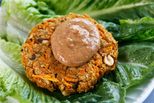 This vegan chickpea-sweet potato burger is topped with peanut butter sauce.