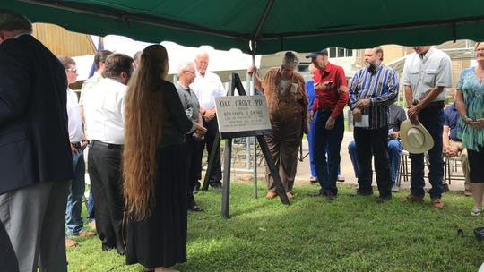 Members of the Drake family, including Ben and Cecil Drake, Benjamin Drake's grandsons (right of plaque) unveil a memorial to Drake that be displayed at the Oak Grove Town Hall.