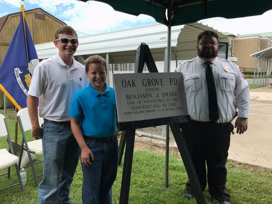 Lieutenant Lee Drake of the Richmond, Mississippi Police Department helped unveil a plaque honoring his great-grandfather Benjamin Drake. Also pictured are Lee Drake's two sons.