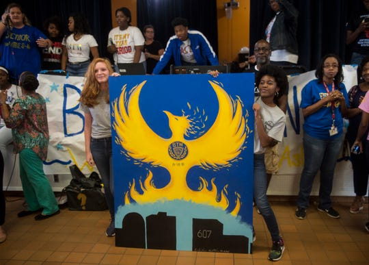 Erika Lewis, left, and Alanna Johnson show off their mural during a pep rally at BTW Magnet School at Hayneville in Montgomery, Ala., on Friday, Aug. 31, 2018.