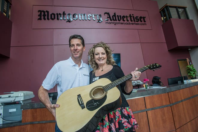 Michael Galvin, president of Montgomery Advertiser, presents Tammy Noah of Clanton a guitar signed by country music star Jake Owen, along with a copy of Owen's Greatest Hits CD.