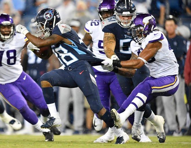 Minnesota Vikings linebacker Reshard Cliett (43) hangs onto Tennessee Titans running back Akrum Wadley (38) during the second quarter of a preseason game at Nissan Stadium Thursday, Aug. 30, 2018, in Nashville, Tenn.
