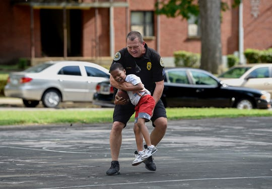 Sgt. Marty Reed with the Metro Nashville Police Department tackles Denzel Bigham, 7, as they play football in the Cayce Homes housing development in Nashville on Thursday, Aug. 30, 2018.