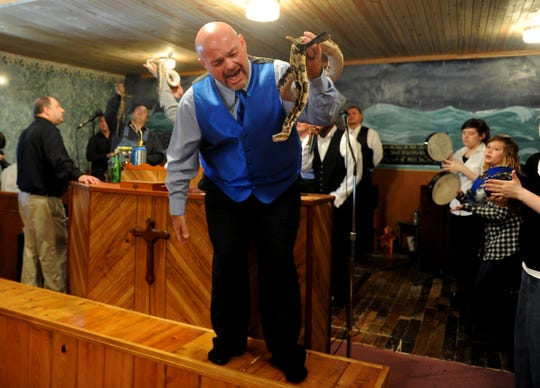 In this May 6, 2012 file photo, Jamie Coots, pastor of the Full Gospel Tabernacle in Jesus Name Church of Middlesboro, Ky, stands on a bench before the church, singing and holding a rattlesnake during service at Tabernacle Church of God in LaFollette, Tenn. Coots died in 2014 after a snake bite.