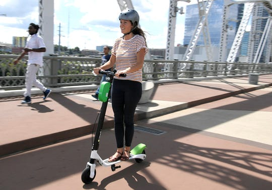Jessica Burton with Walk Bike Nashville rides a Lime electric scooter on the John Seigenthaler Pedestrian Bridge during Lime's Nashville launch on Friday, August 31, 2018.